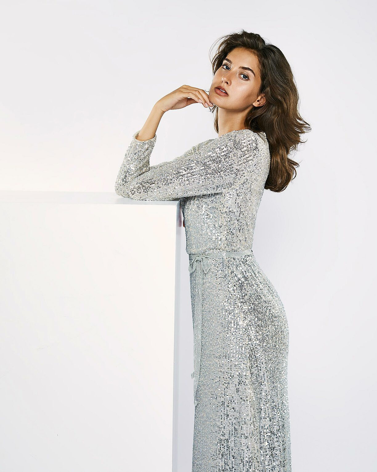 A brown hair model in a sparkling silver dress stand in a white setting