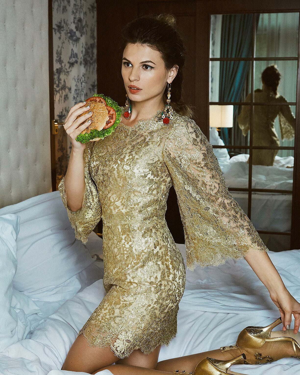 A model wth brown hair wears big earrings and knees on the bed in a golden dress with golden shoes. She hold a burger in her right hand.
