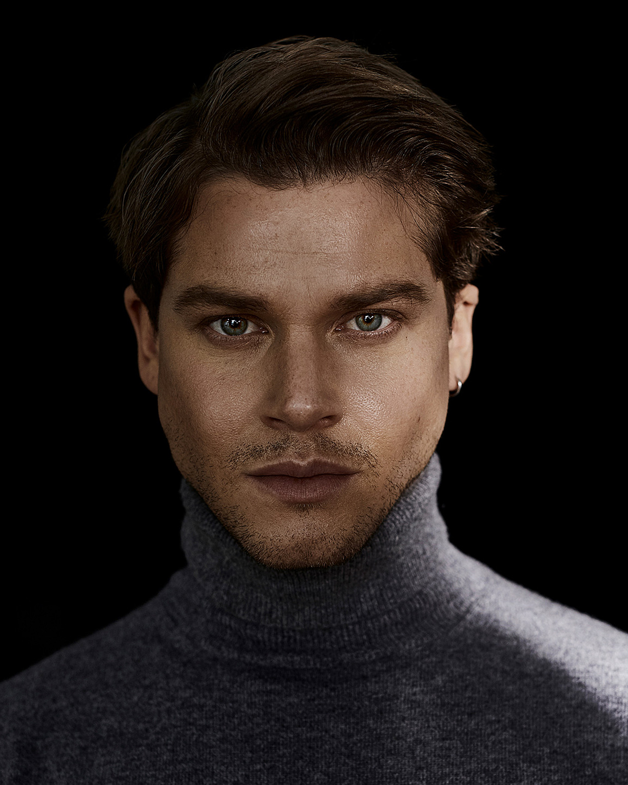 A portrait of a male model who wears a grey pullover with a turtle neck.