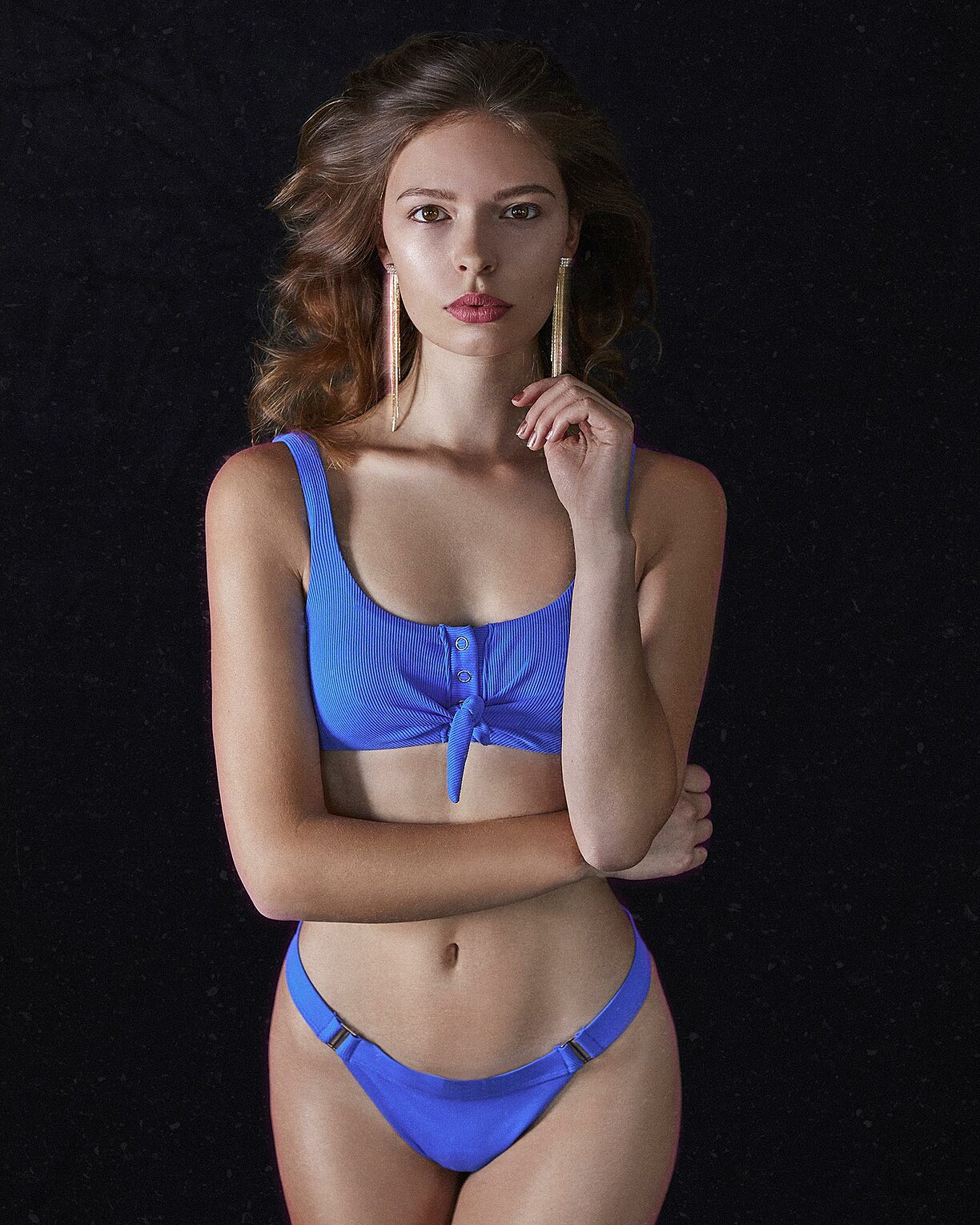 A light brown hair model with long earrings and a blue bikini