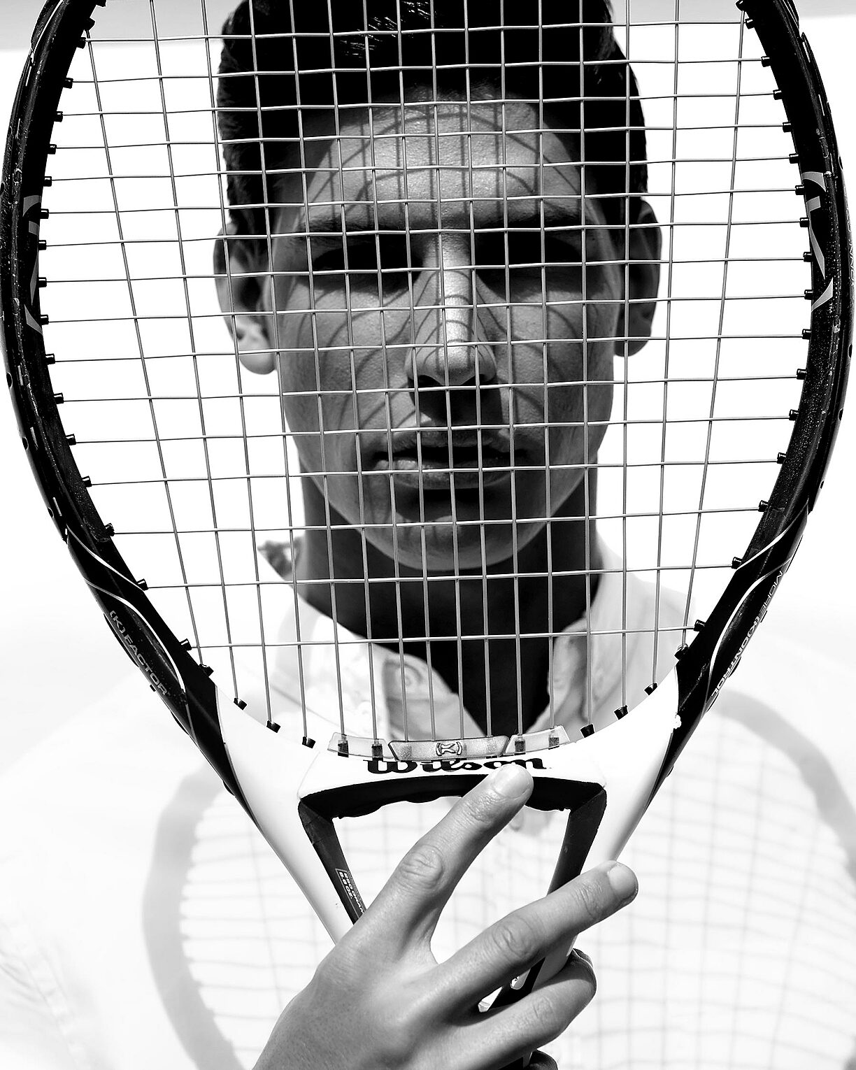 A black and white picture with a male model in a white shirt. He hold a tennis rocket in his right hand in front of his face
