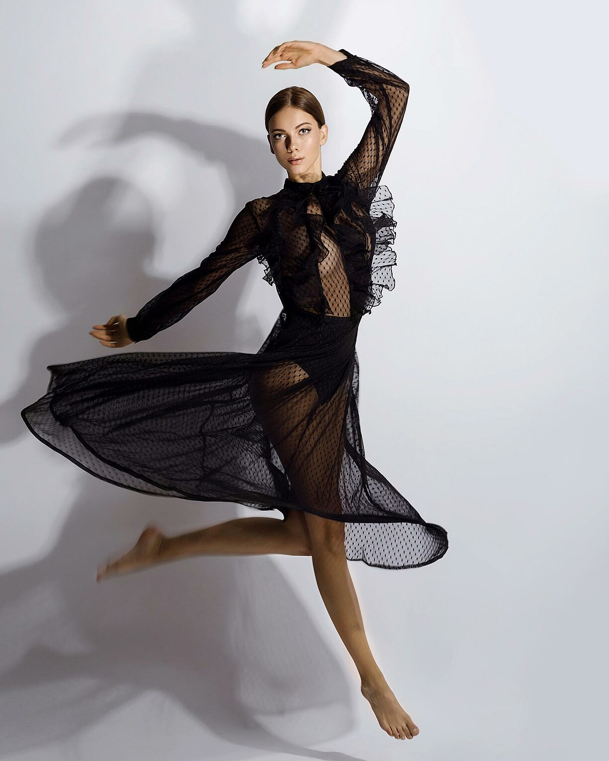 A brown hair model who jumps in a transparent black dress like a ballerina