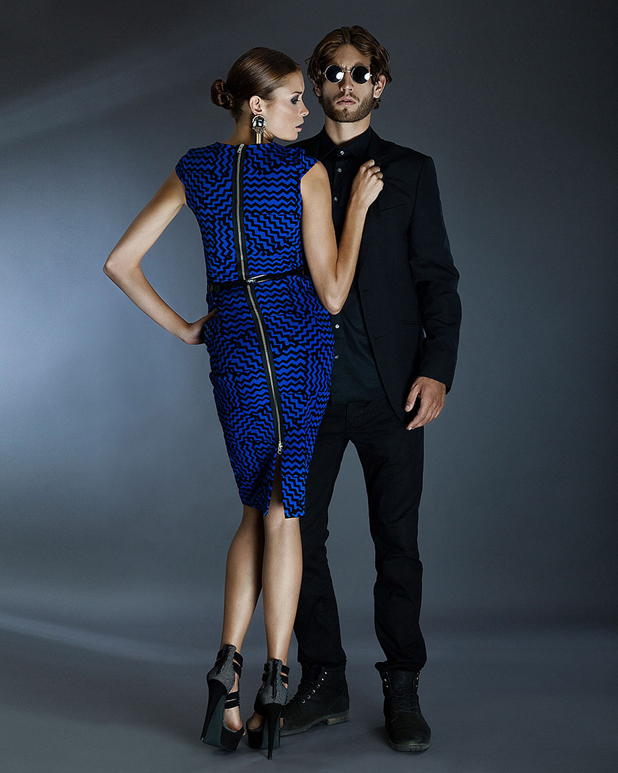 A couple stand in front of each other. The man with black sunglasses in a black outfit and the women in a blue tight dress with a long zip and black high heels