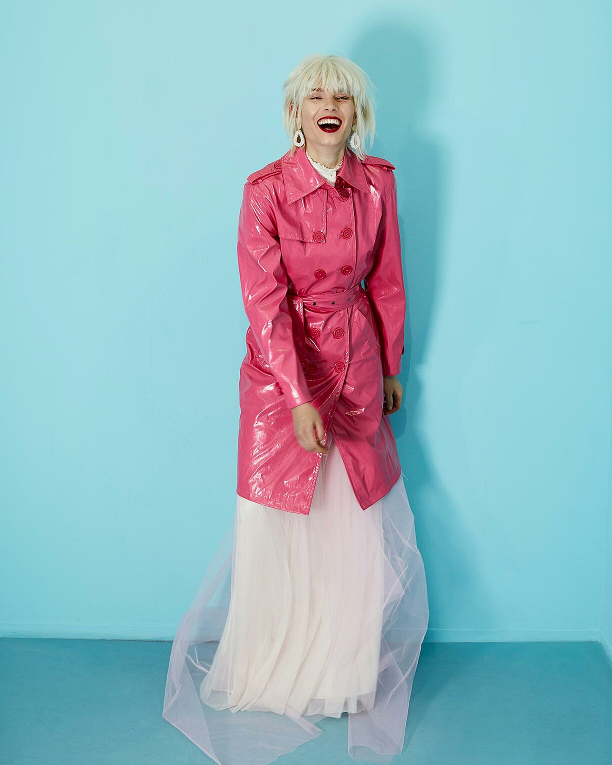A model with blonde wings in a pink trench coat. She wears under the coat a pastel rosy dress and laughs into the camera