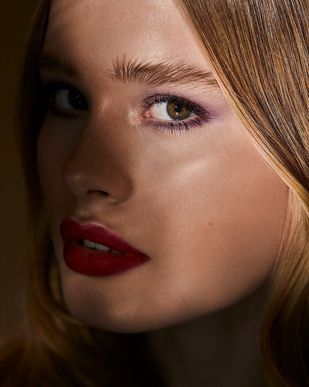A beauty close-up with a blonde model. She wears red lips and a light purple eye shadow. A shadow is around her nose