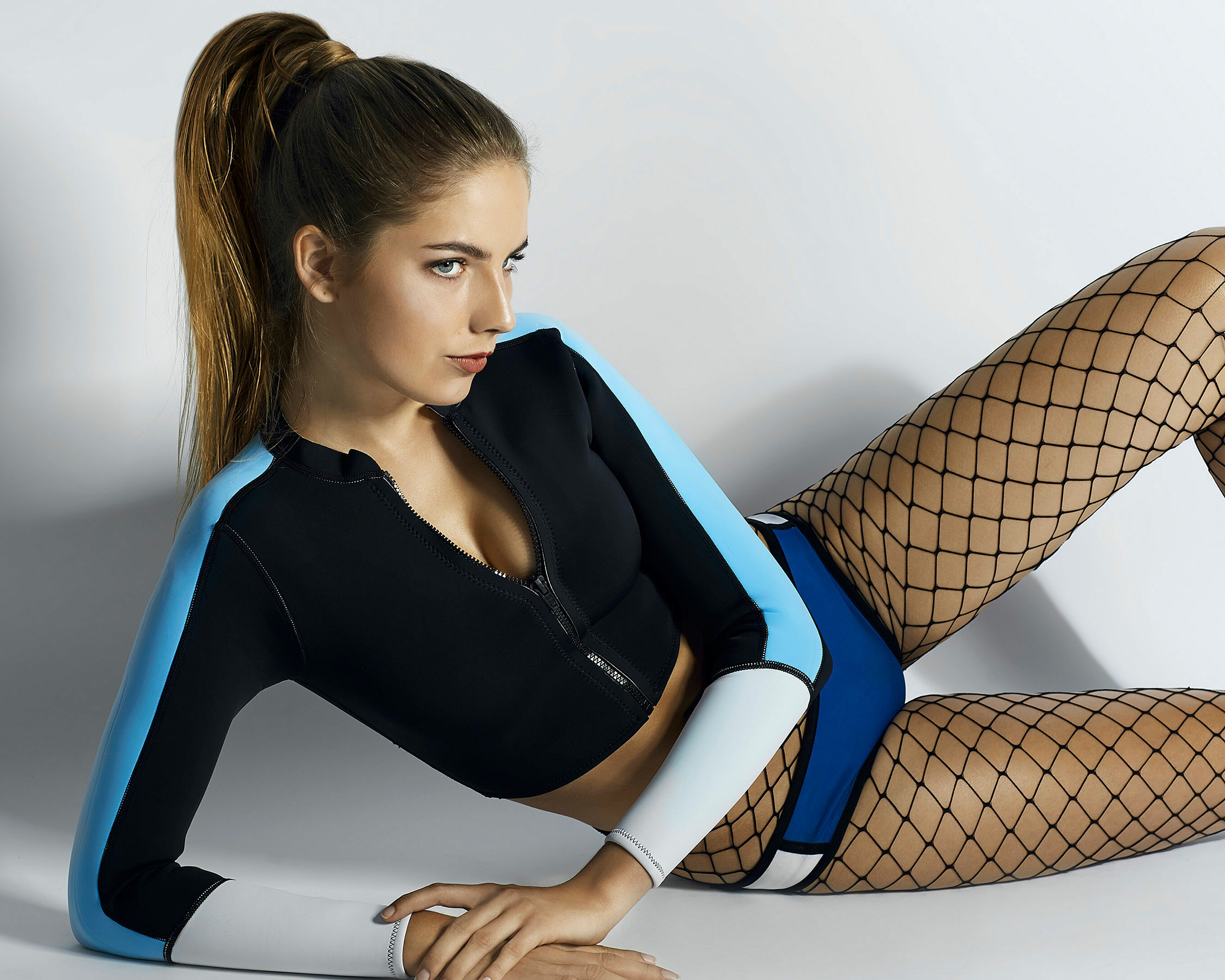 A women laying on the ground in a sit up position with a blue colored neoprene swimwear and mesh tight. Her ponytail is in the focus.