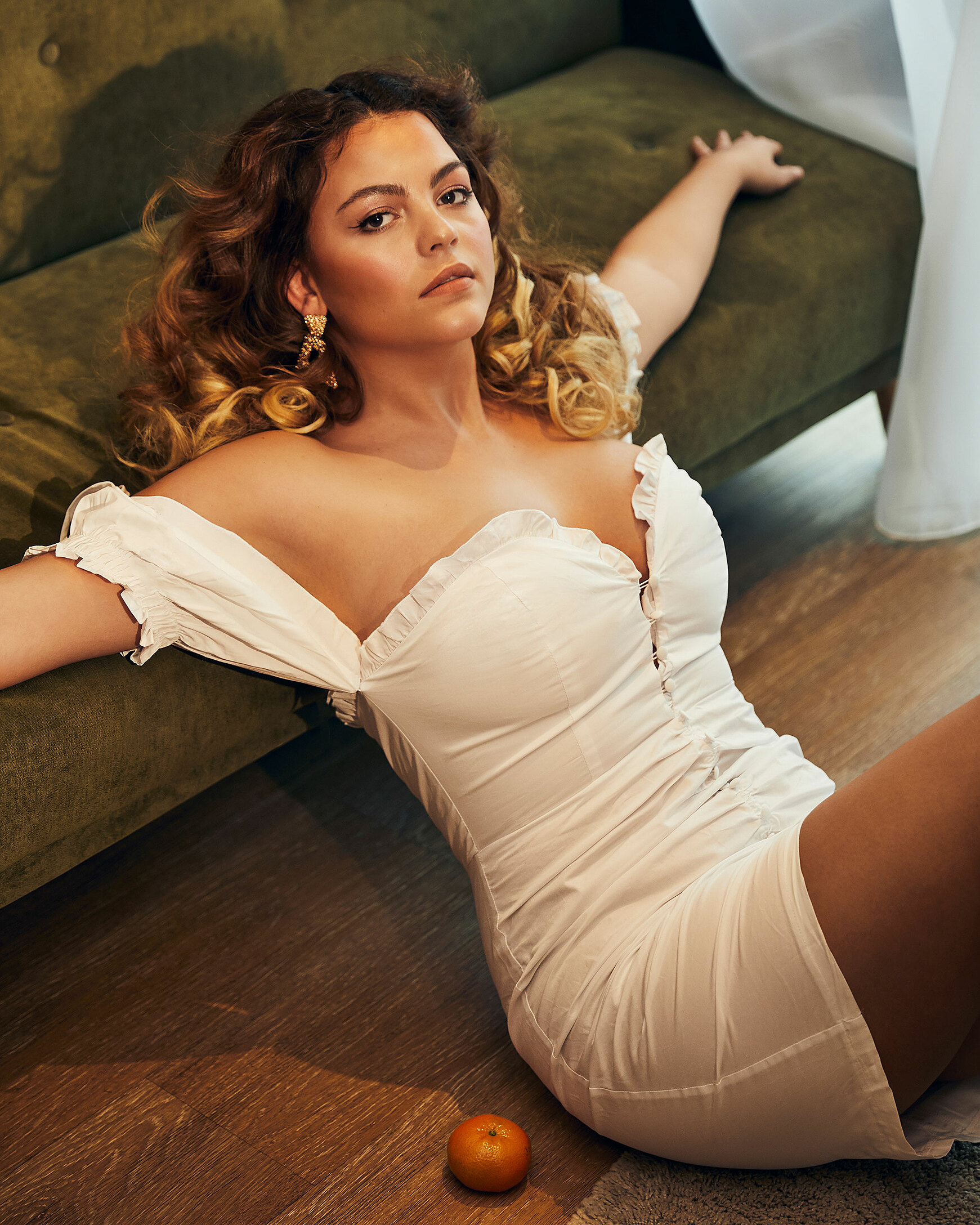 A brown hair model with curly hair in a white dress. She sits on the ground and lean against the sofa with a tangerine next to her