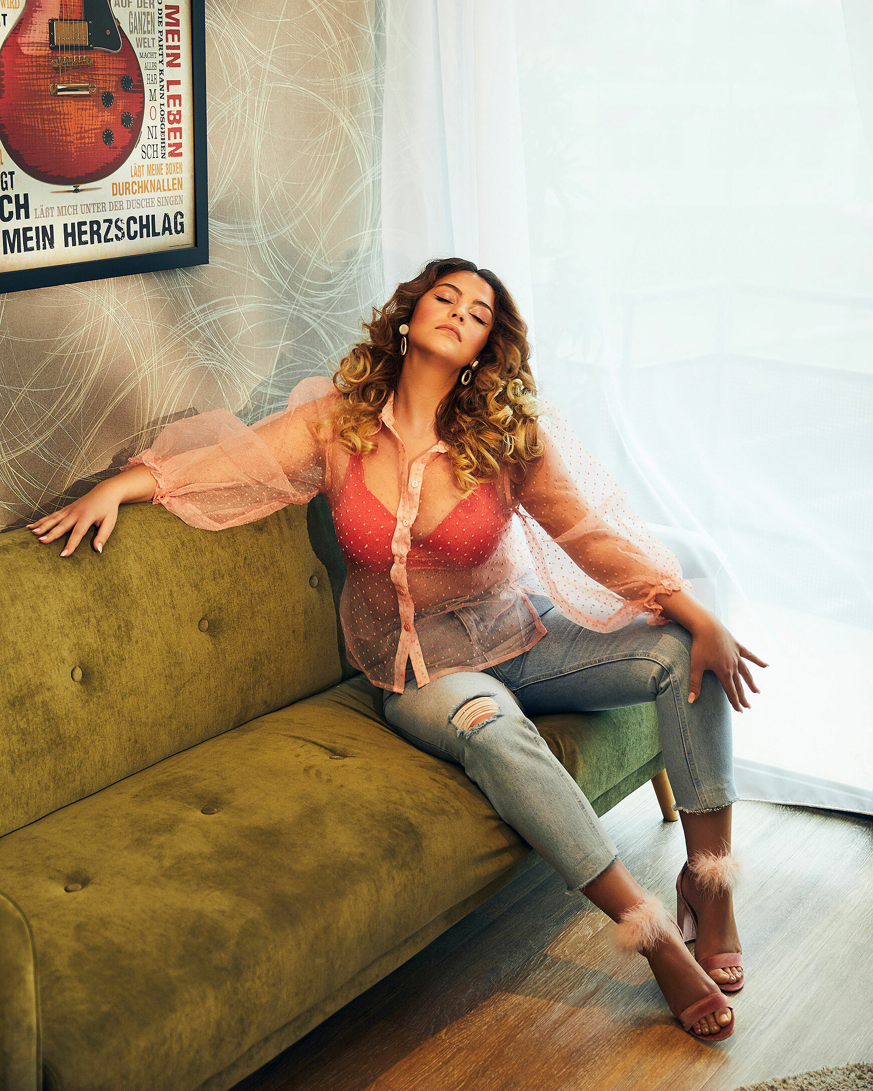 A female model with big curly hairs and a blue denim with rose high heels sits on a green sofa with a rosy blouse in a hotel room