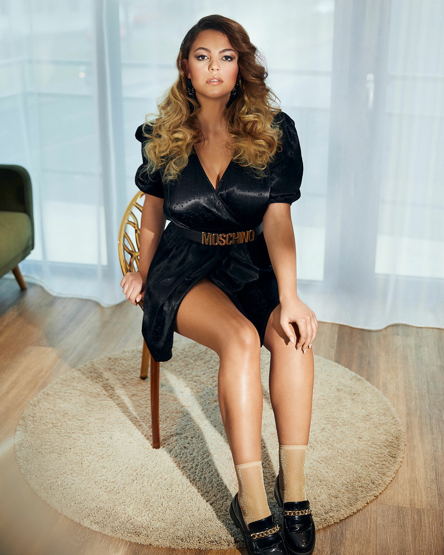A brown hair model sits on a brown chair in front of the camera She wears a black dress and a golden moschino belt. Her pair of socks are golden. She wears them with black shoes