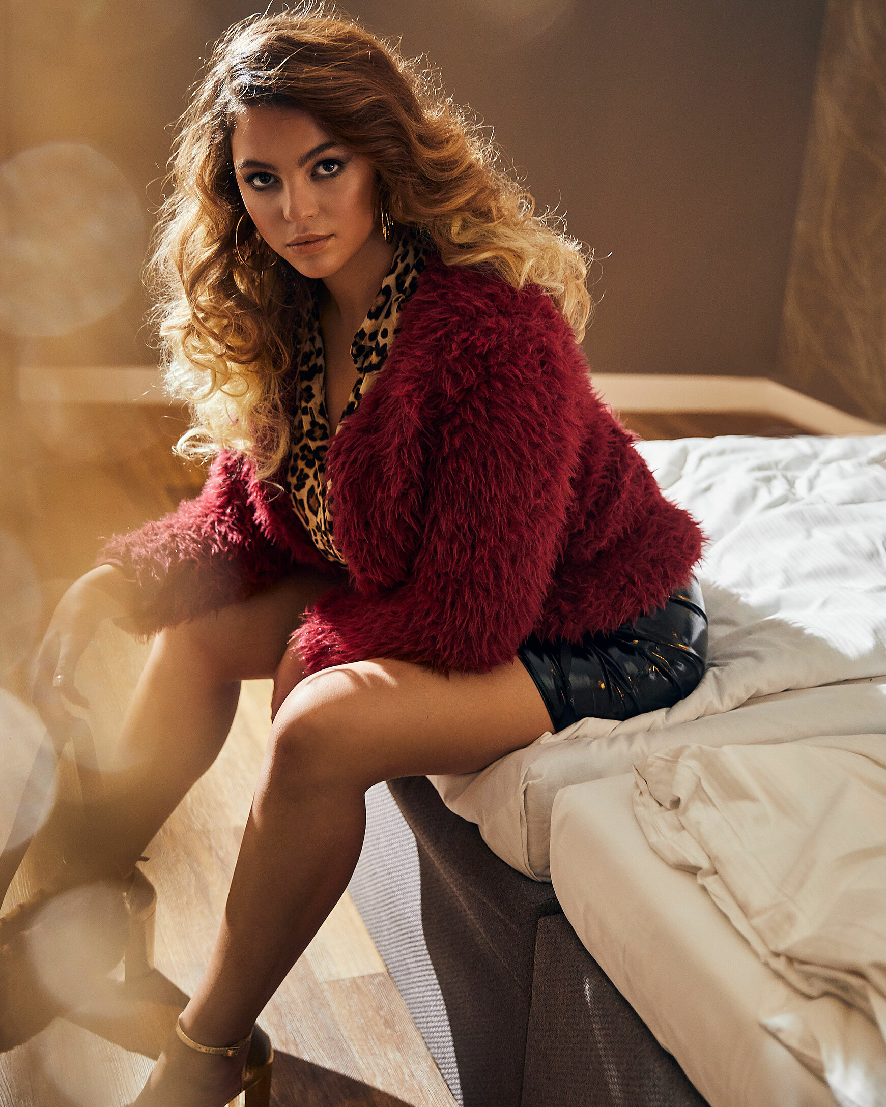 A brown hair model sits on bed in a blackberry teddy jacket with a black skirt and a blouse with leopard print