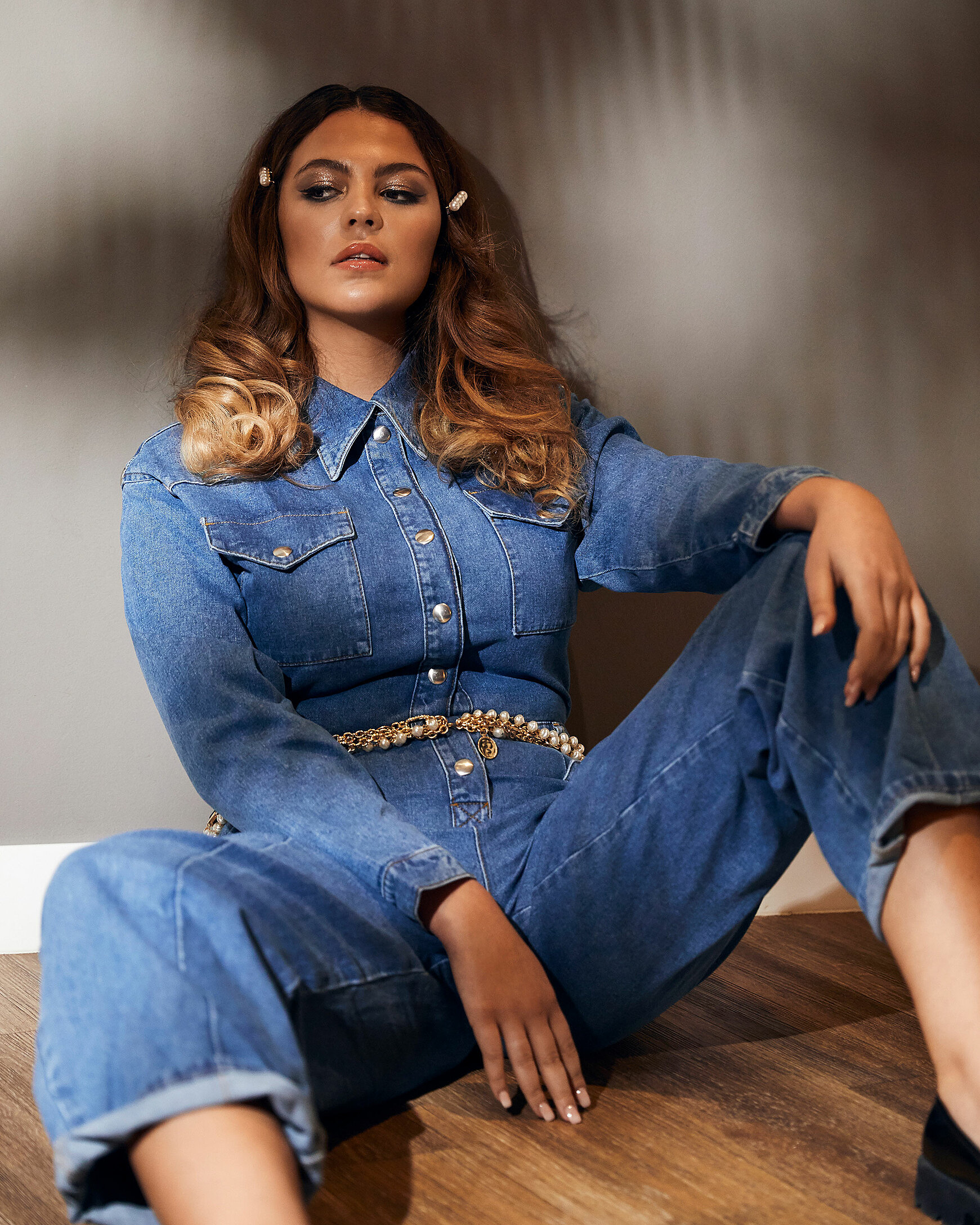 A brown hair model sits on the floor in a denim jumpsuit with a golden belt around her hips. Two white pearl clips complete her hairstyle