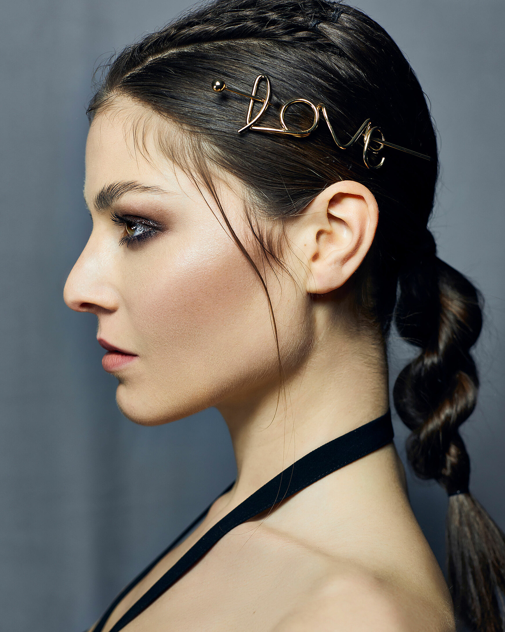 A close-up of a female model with brown hair darf eyeshadow and a creative bun with barrette which spell love.