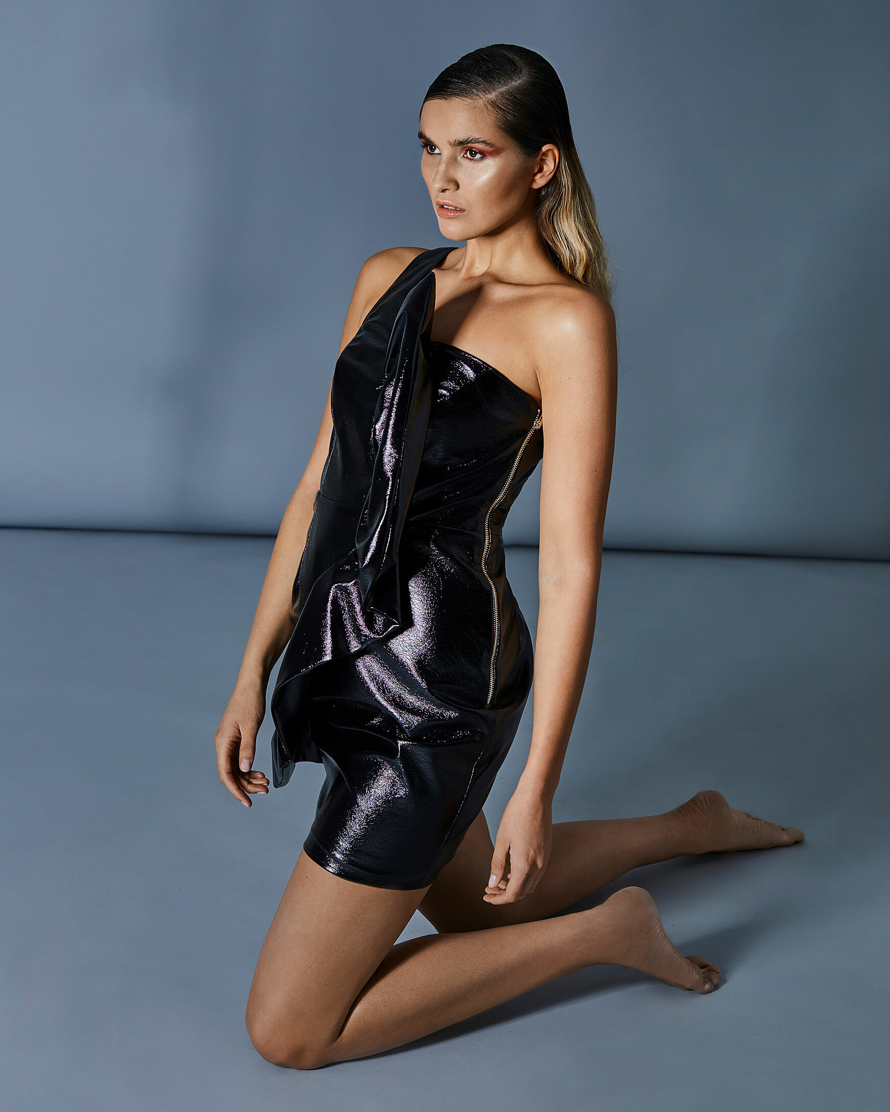 A female model knee on the ground in a strong pose with a black one-shoulder dress