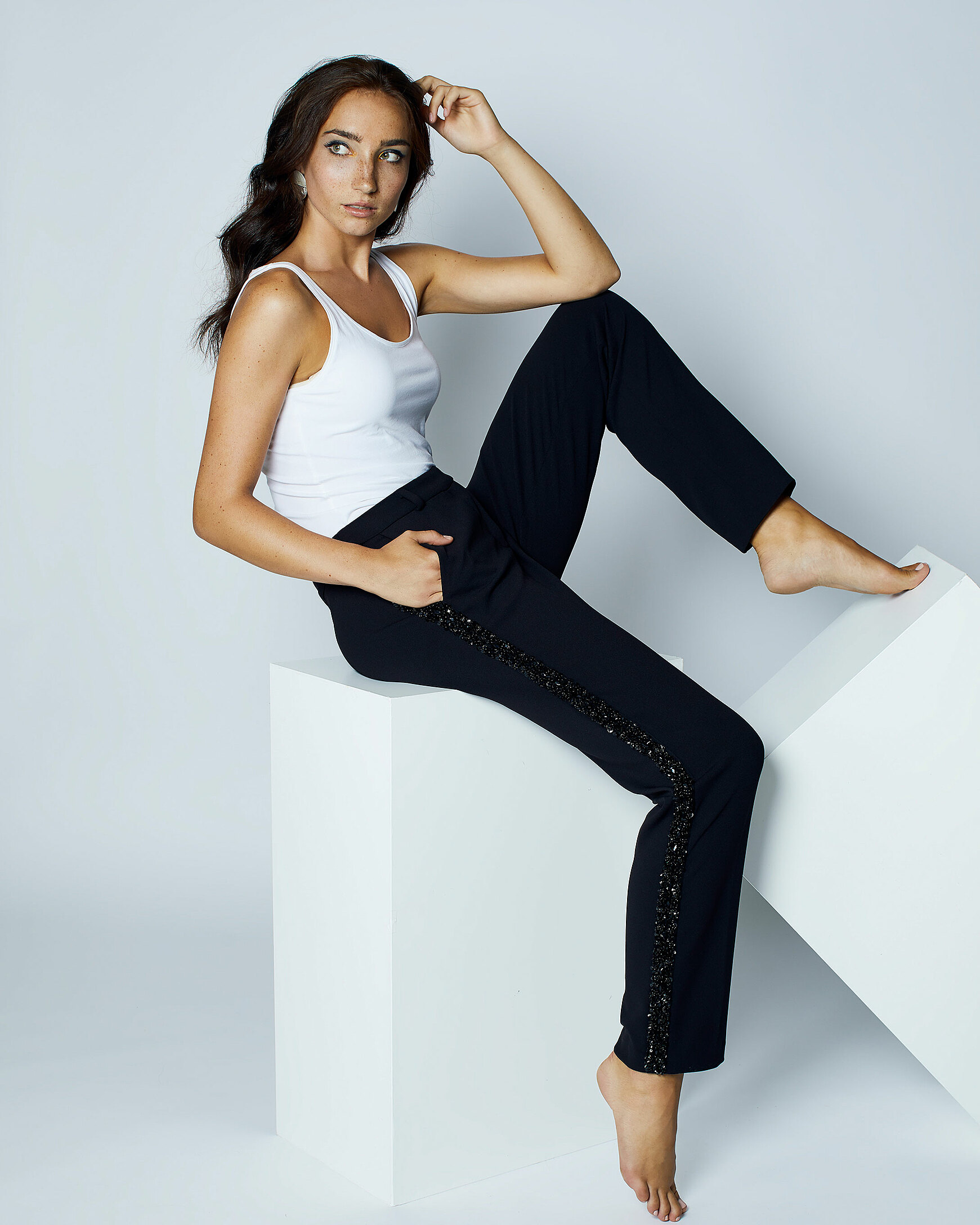 A brown hair model with a freckles face who wears a white top and black trousers with nacked feet