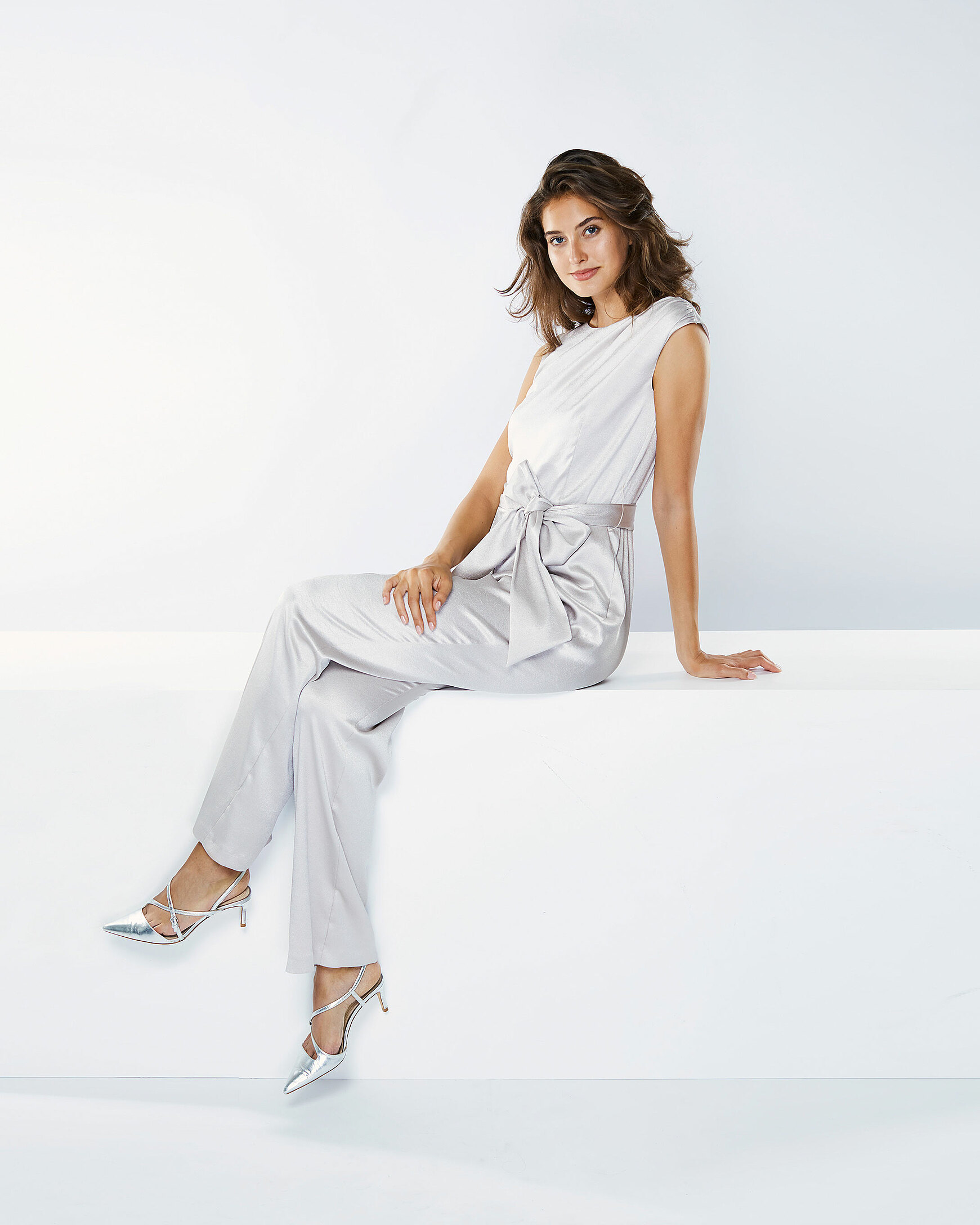 A brown hair model in a silver overall sits in a white setting