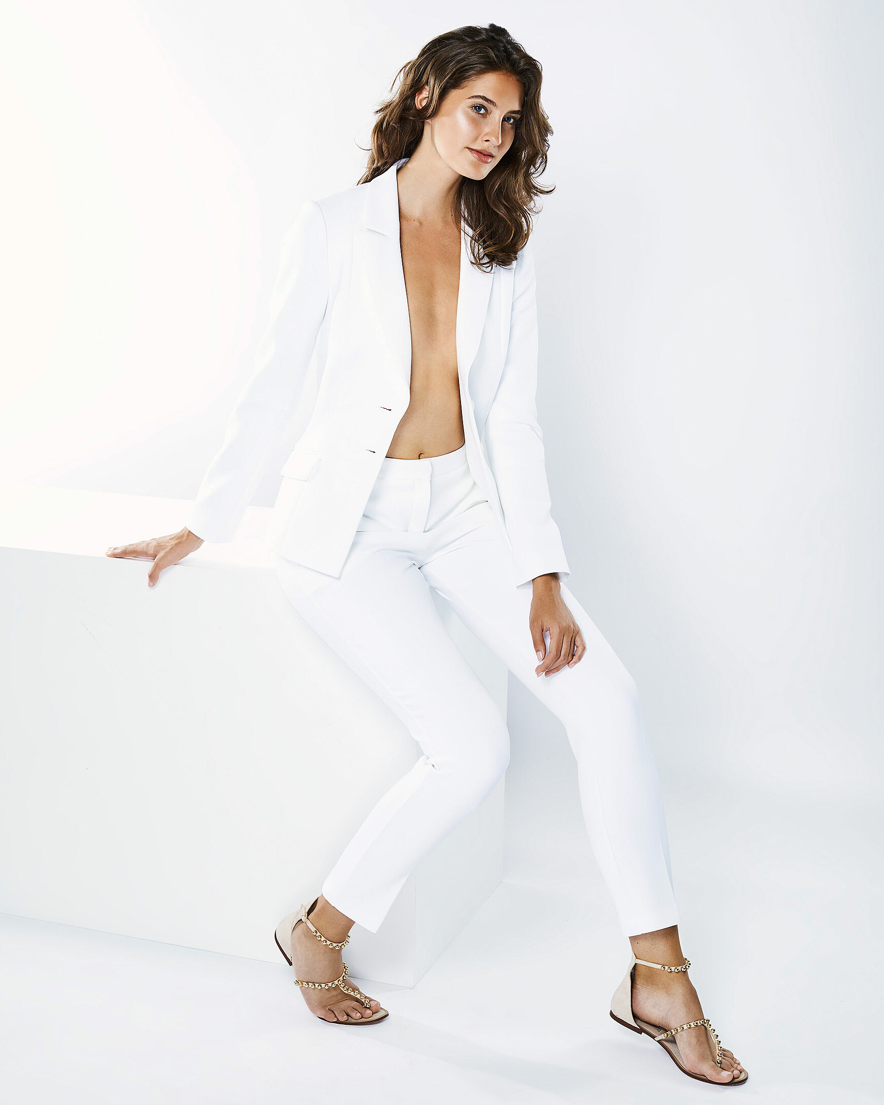 A brown hair model in a white blazer with white tights sits in a white setting