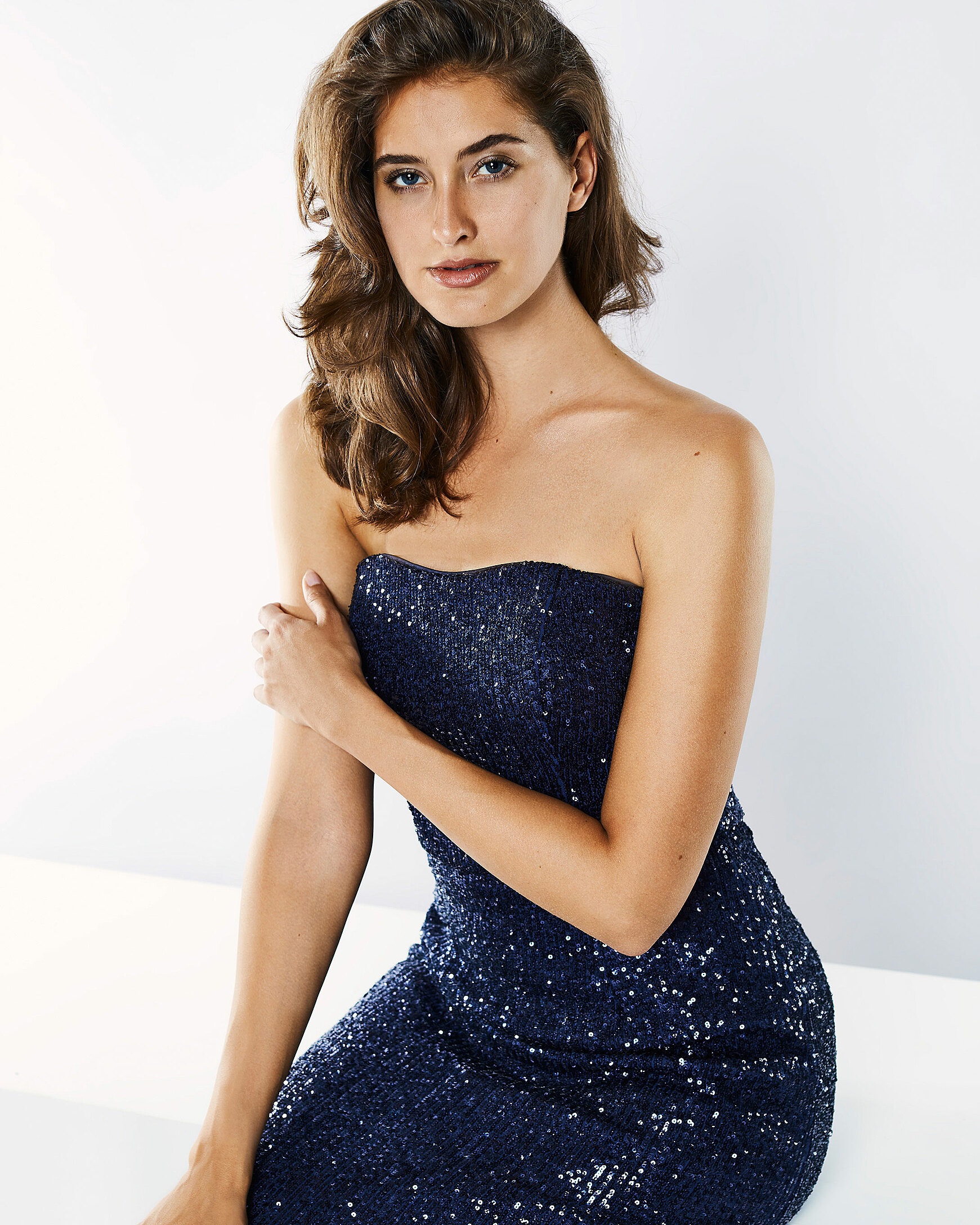 A brown hair model in sparkling blue strapless dress sits in a white setting