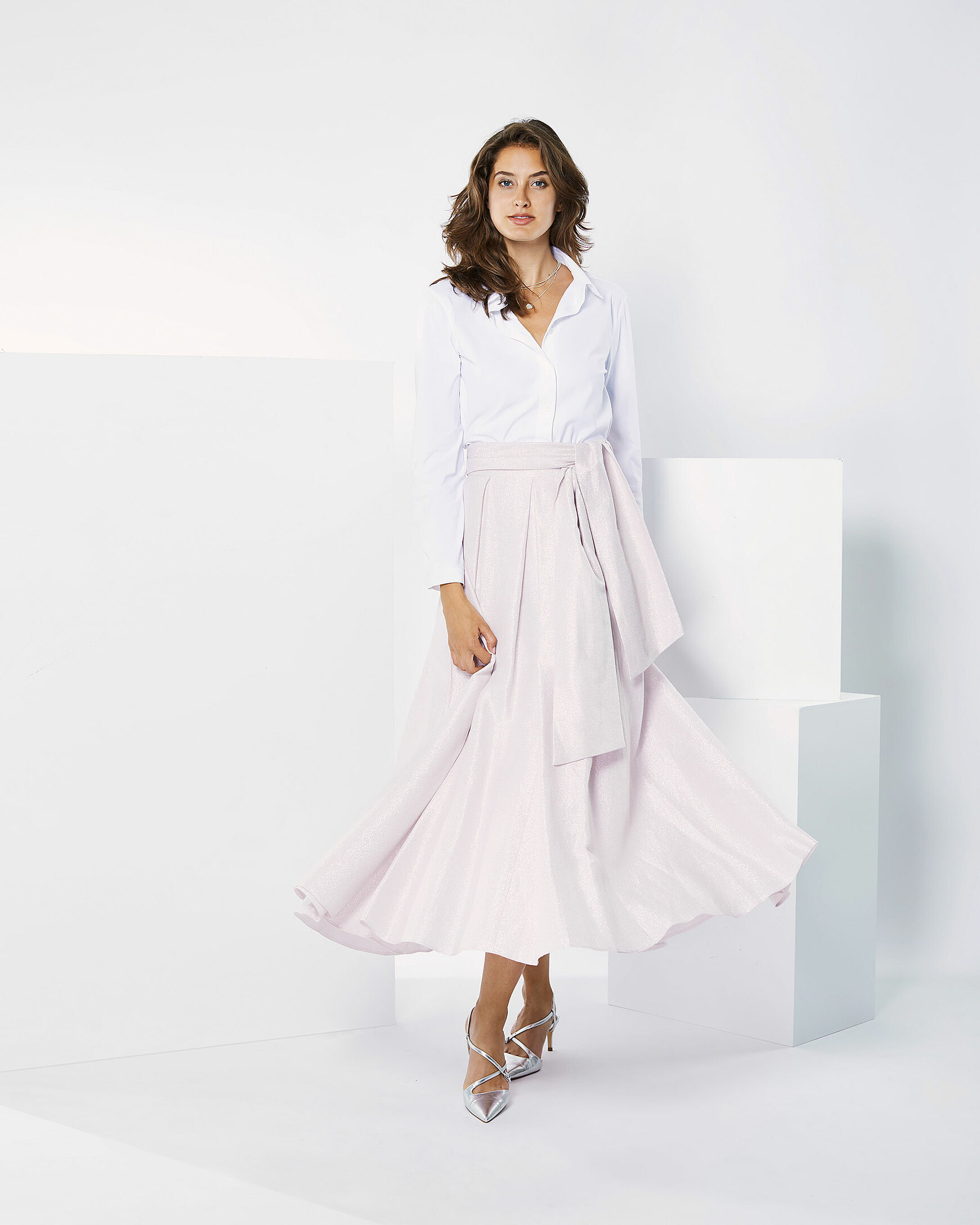 A brown hair model in rosy skirt and a white blouse is moving in a white setting