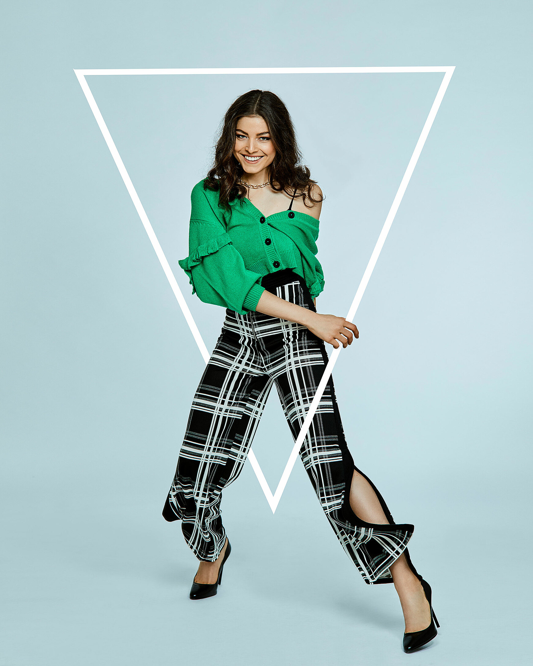 A brown hair model with a green casual jacket and pattern trousers steps through a triangle.