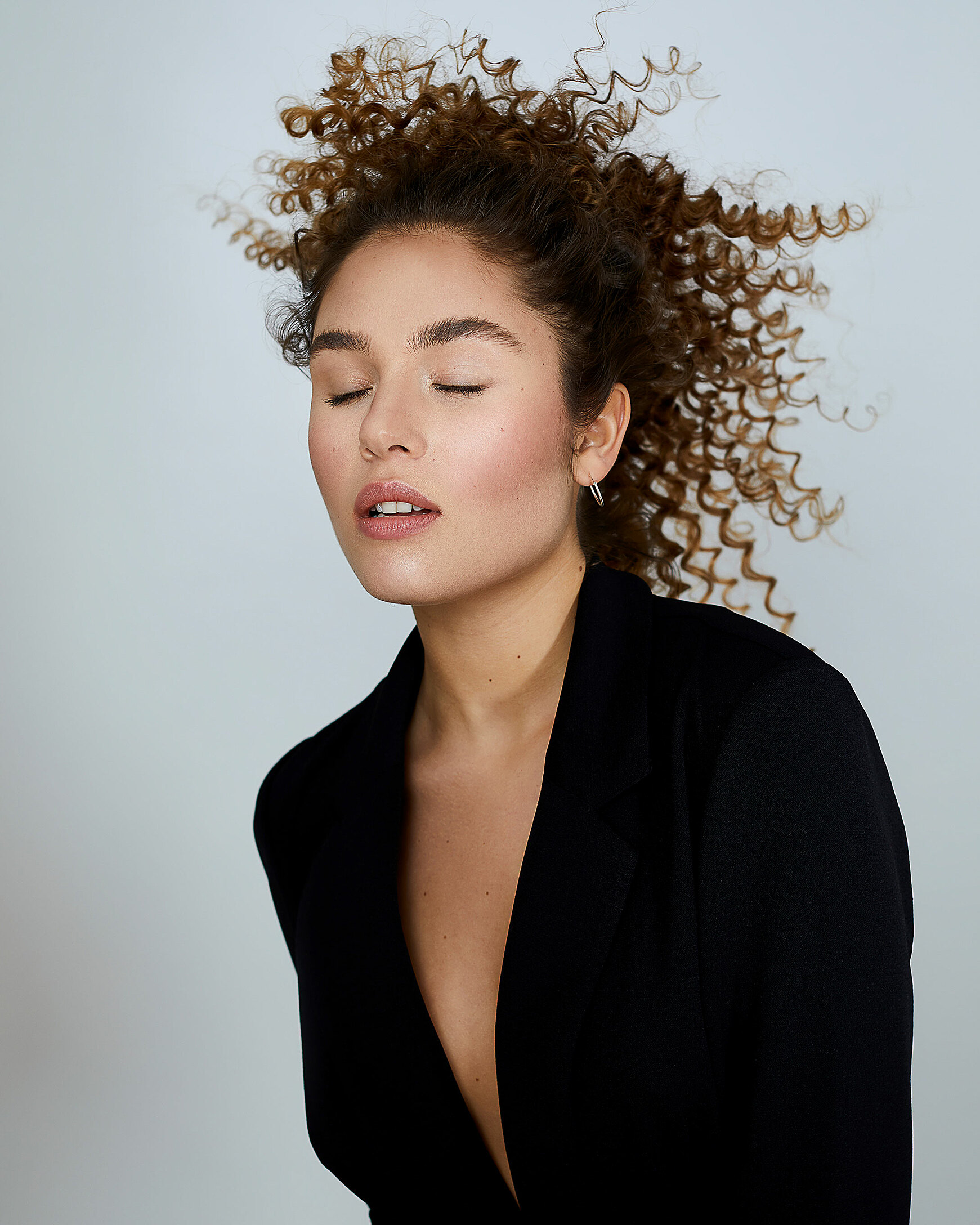 A female model with big curly hair in a bun and a natural makeup. Her hair blows away. She wears a black kimono.