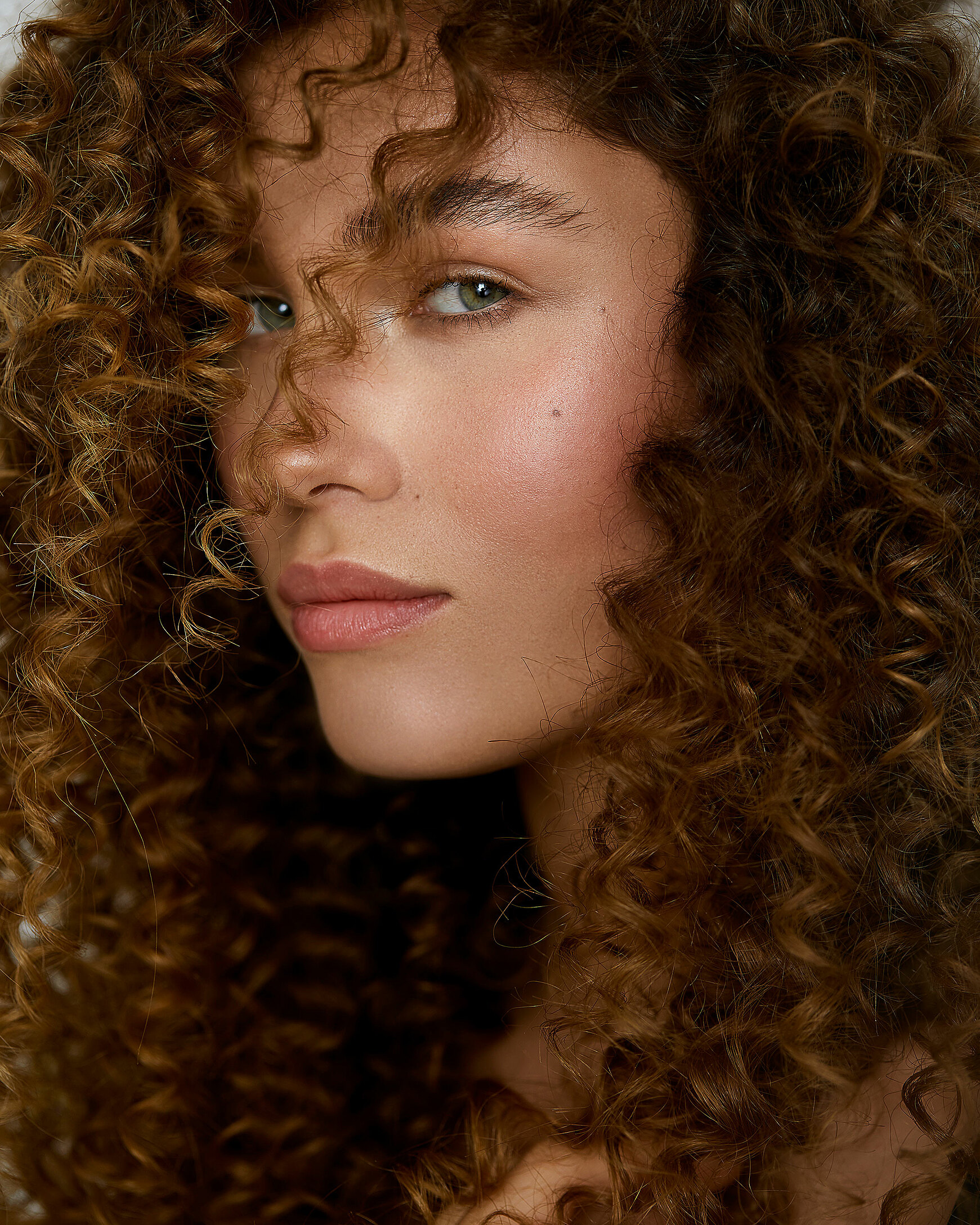 A close-up of a female model with big curly hair and a natural makeup.