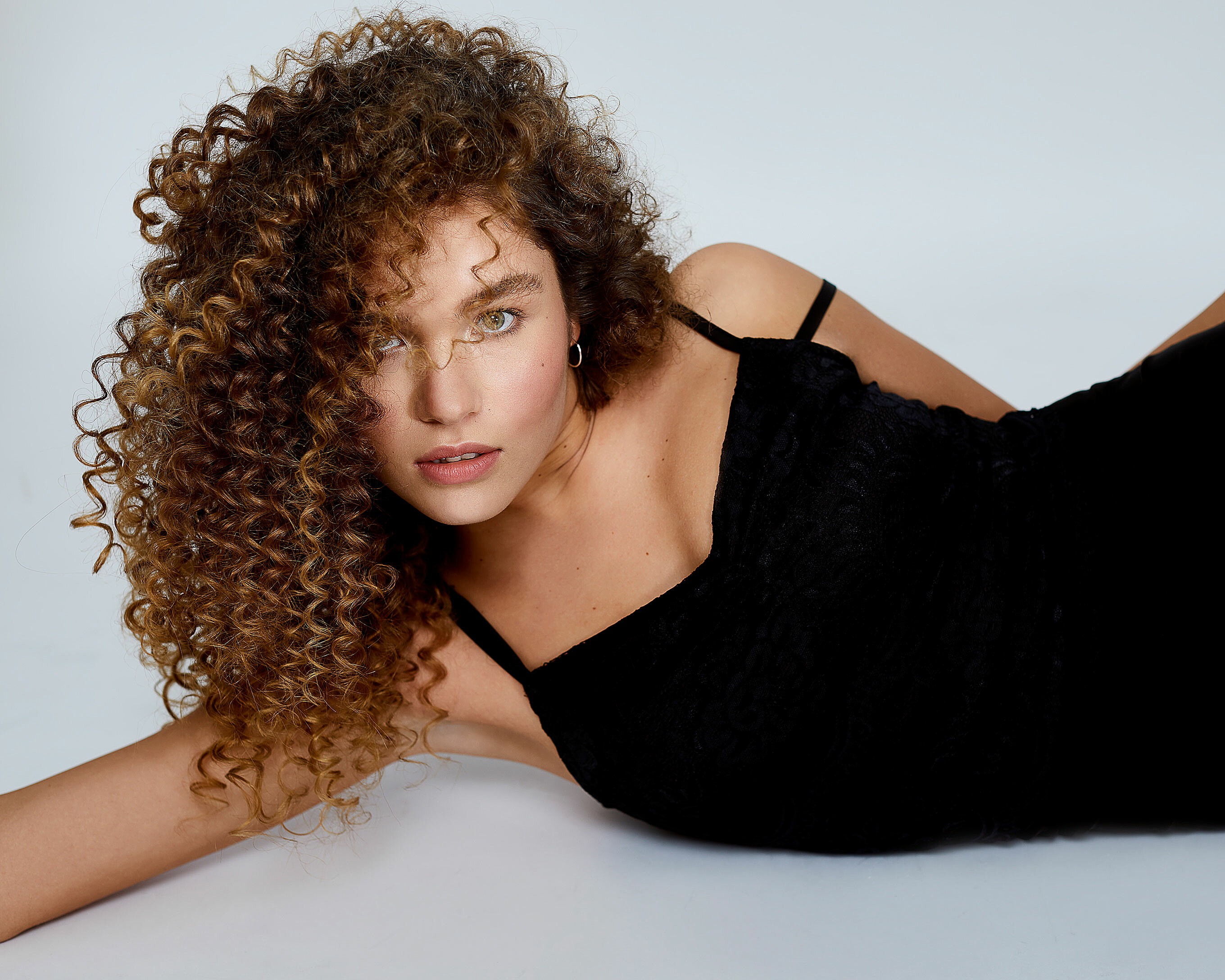 A female model with big curly hair and a natural makeup. Lay on the ground in a bleck dress