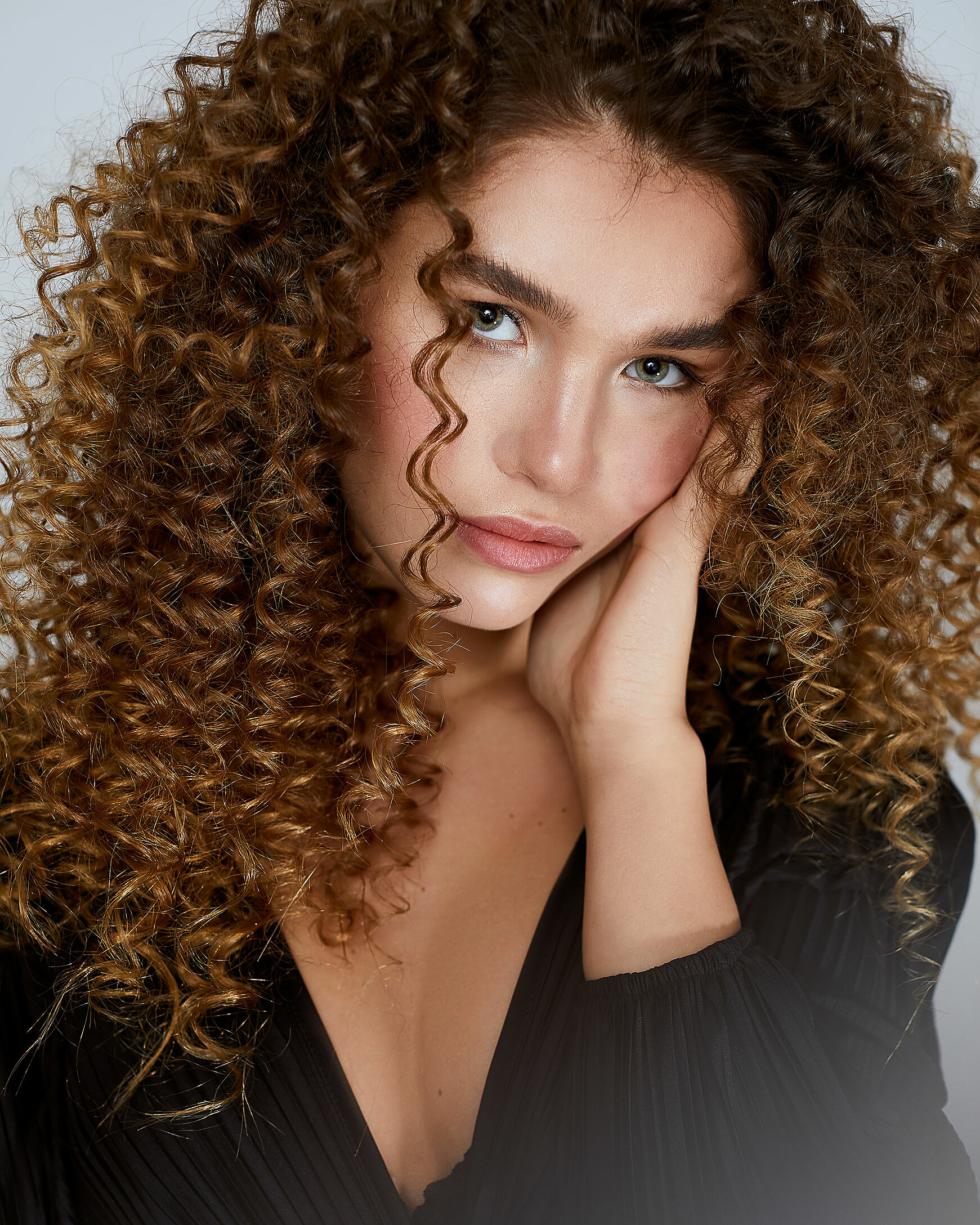 A close-up of a female model with big curly hair and a natural makeup. She wears a black dress with padded shoulders.