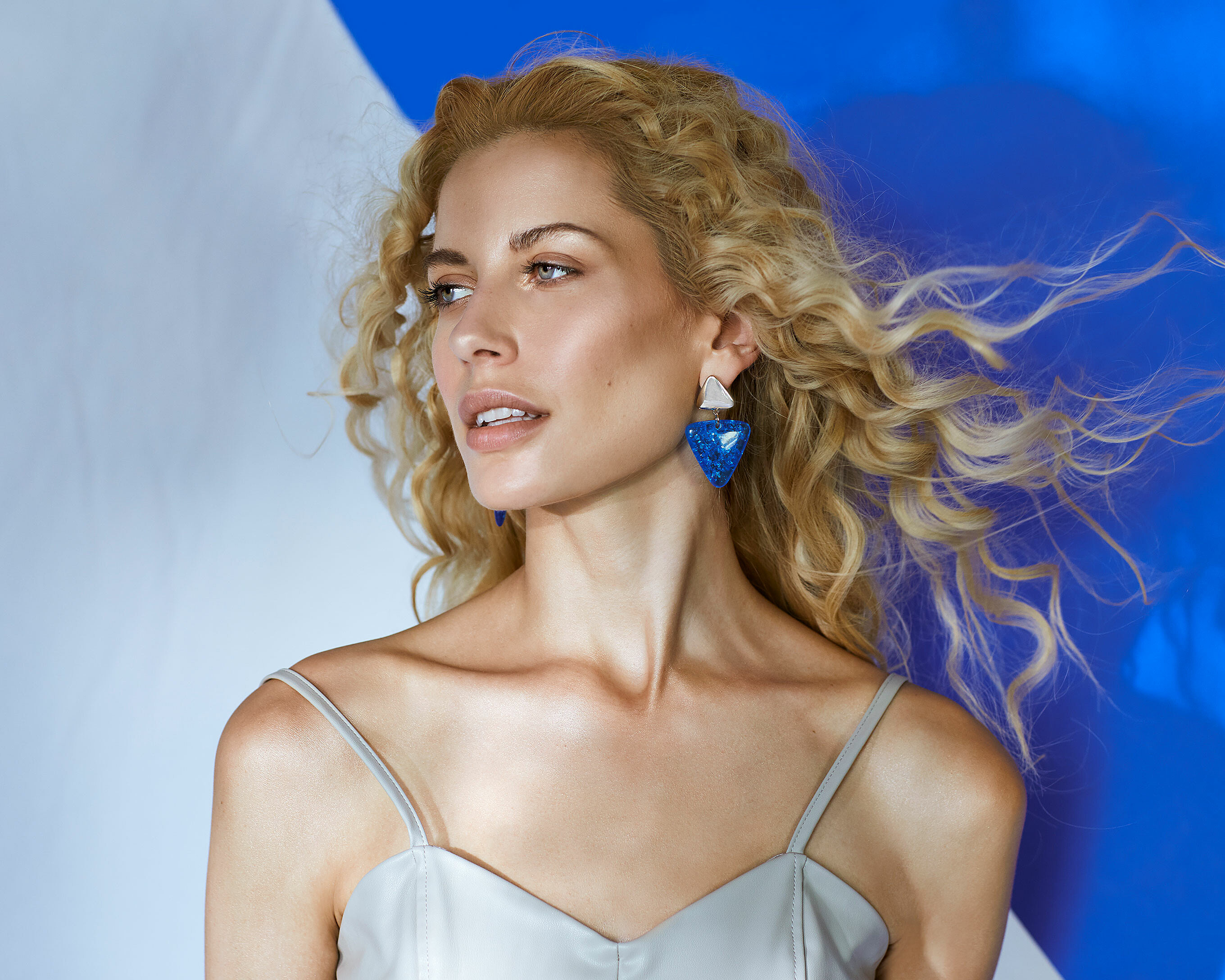 A female model with blonde curly hair stands in front of a white/blue wall. She wears blue earrings and get some wind from the side.