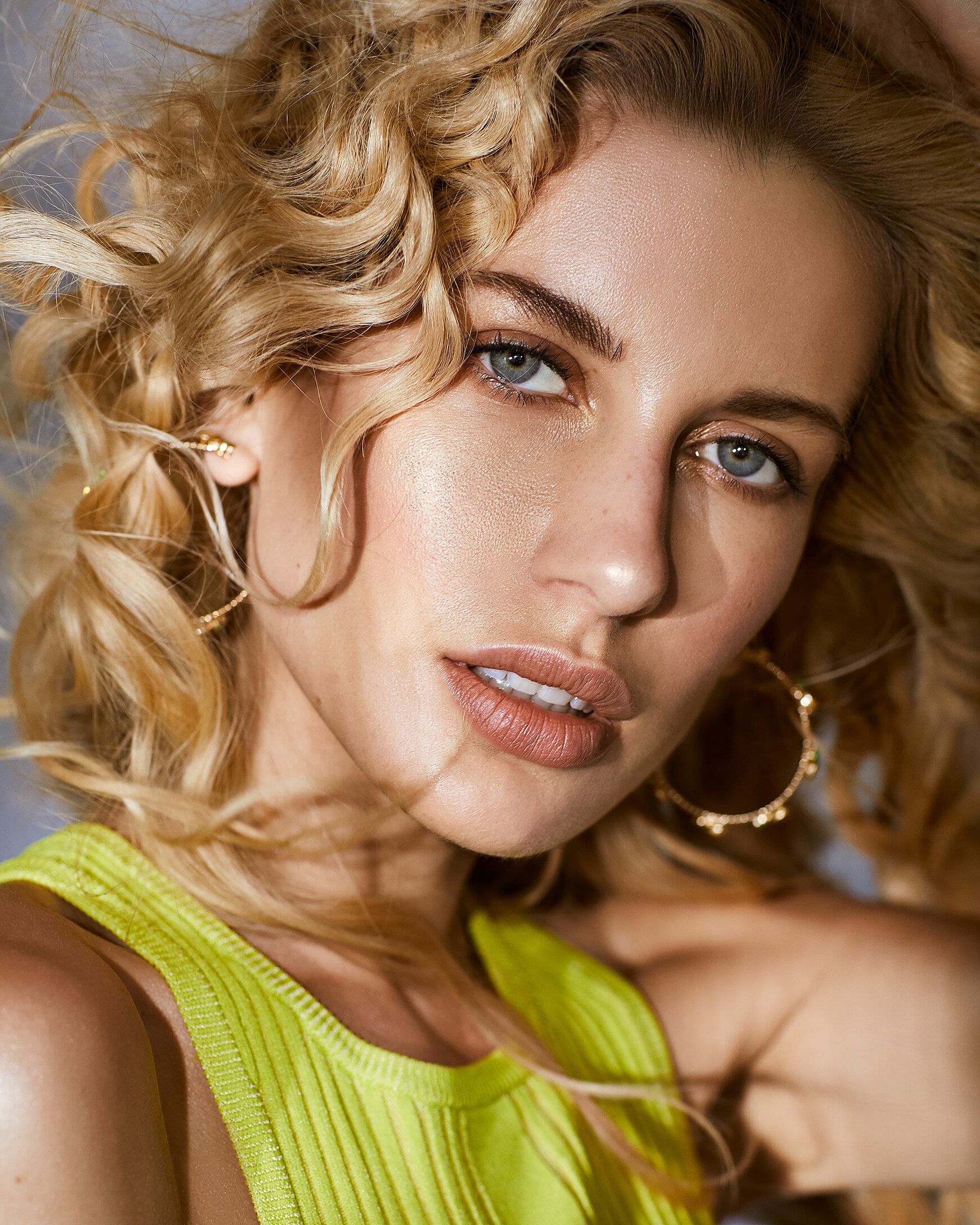 A female model in a citrus yellow crop top with curly blonde hair.