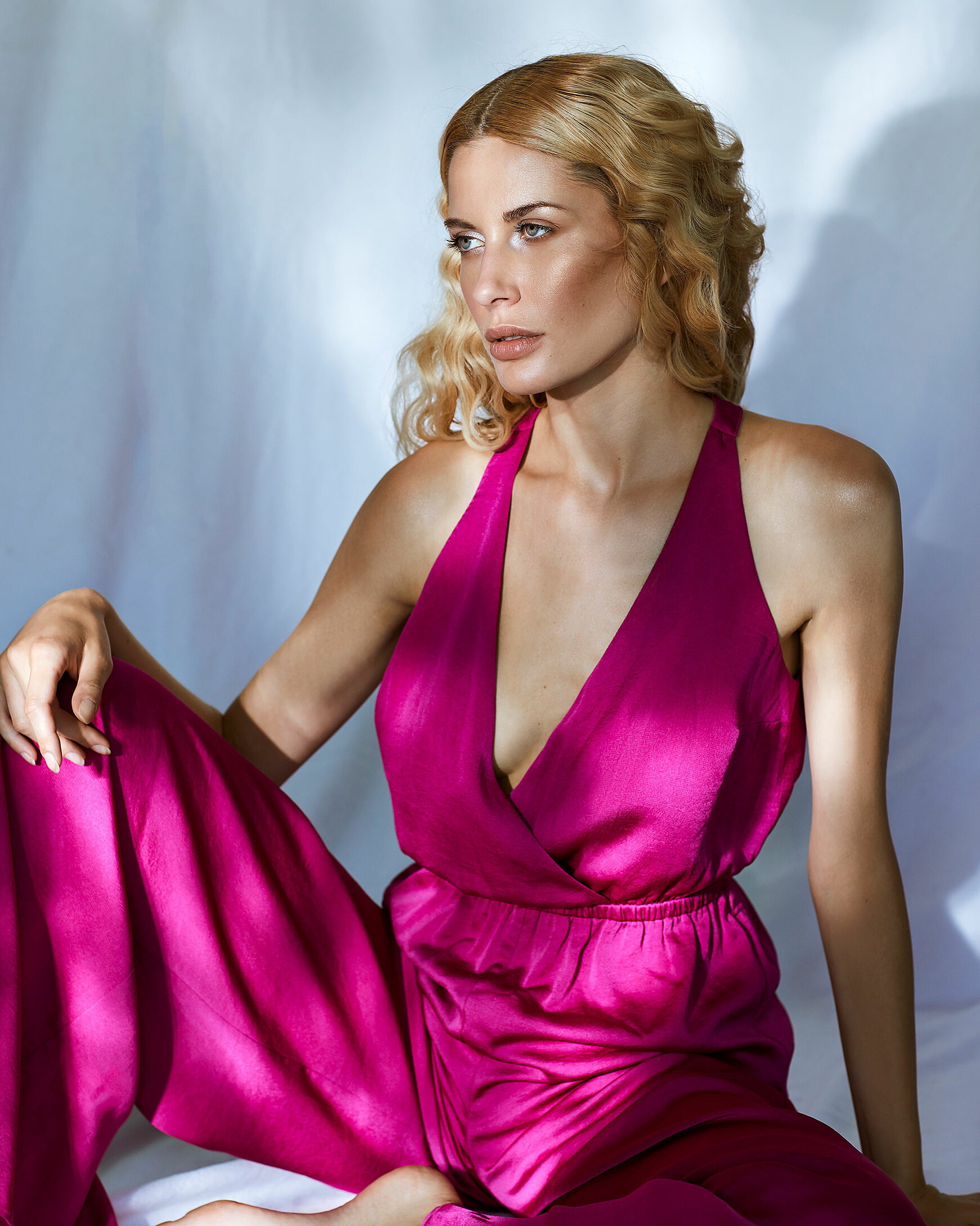A female model with blonde curly hair sits on the ground with a pink jumpsuit.