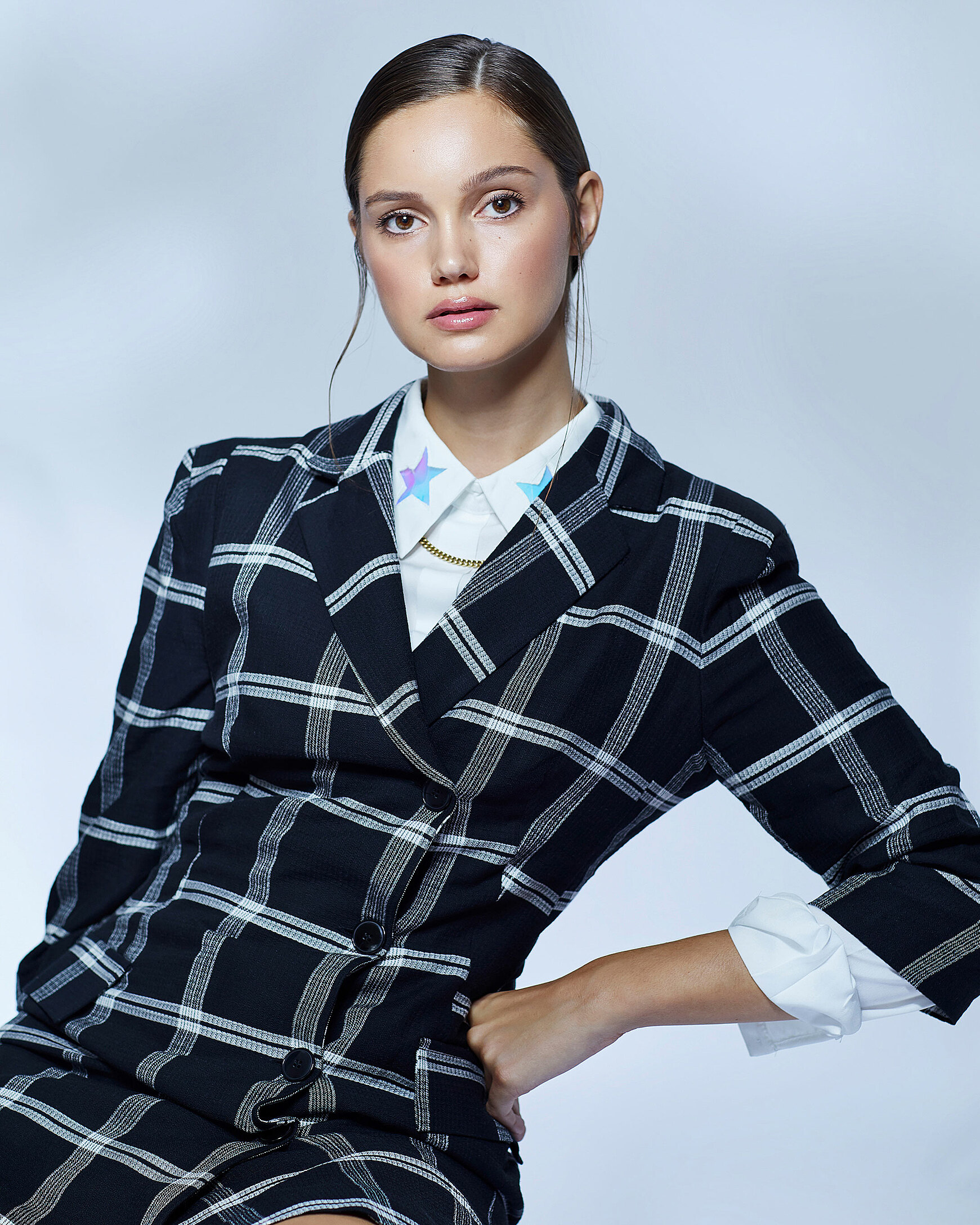 A female model who wears a checked blazer with a white blouse with blue stars on the chocker and sleek brown hair. She looks direct with a strong view into the camera.