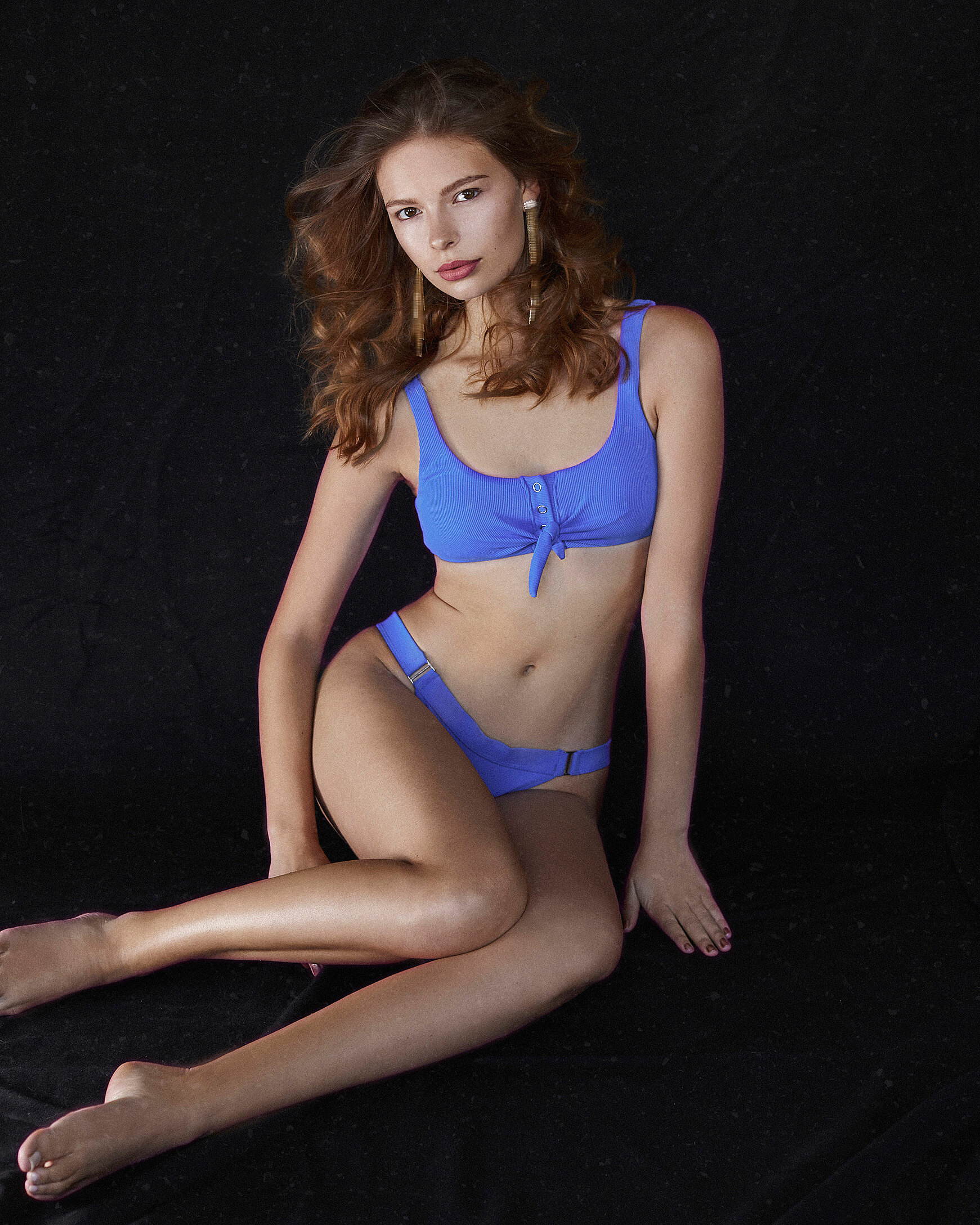 A light brown hair model with long earrings and a blue bikini who sit on a black background