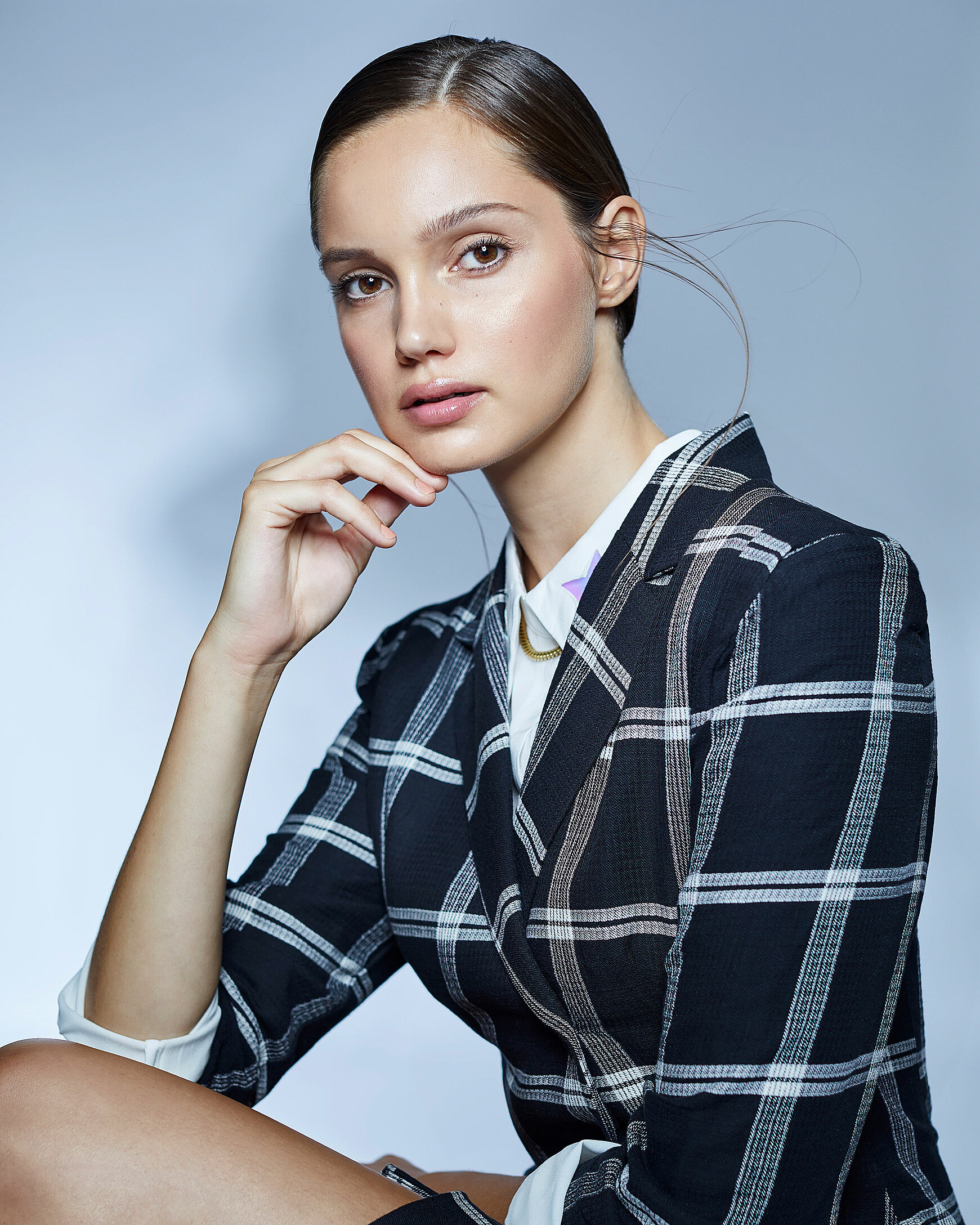 A female model who wears a checked blazer with a white blouse and sleek brown hair who sit in front of the camera