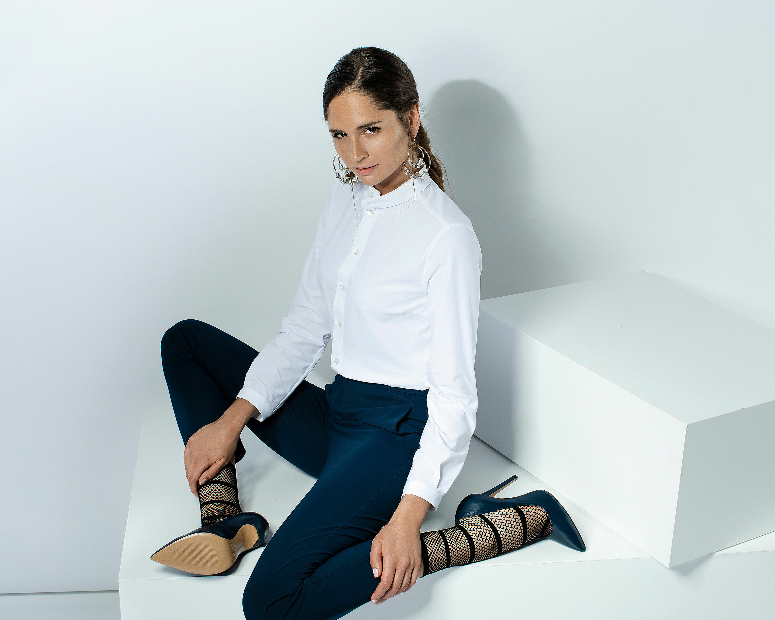 A brown hair model with a strong ponytail who sit in a white indoor location with a white blouse and a skinny blue trousers. Her socks between black stripes and black mesh are inside the blue high heels
