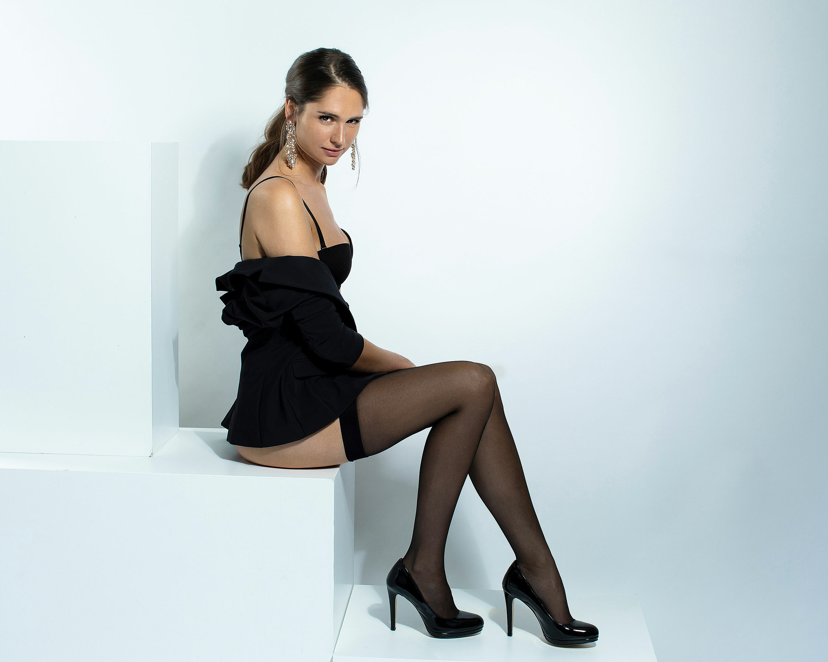 A brown hair model with a strong ponytail wears a black bra and a black blazer with black suspenders in black high heels