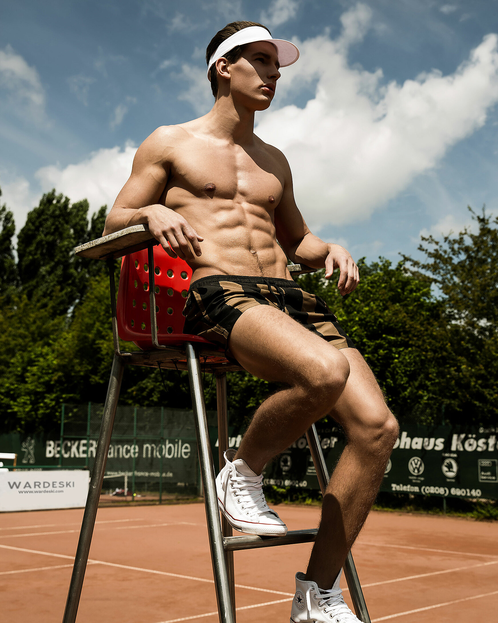 A male model who sit on a red high chair in the middle of the tennis court with a white sunscreen around his head and white chucks. He wears black brown shorts with stripes