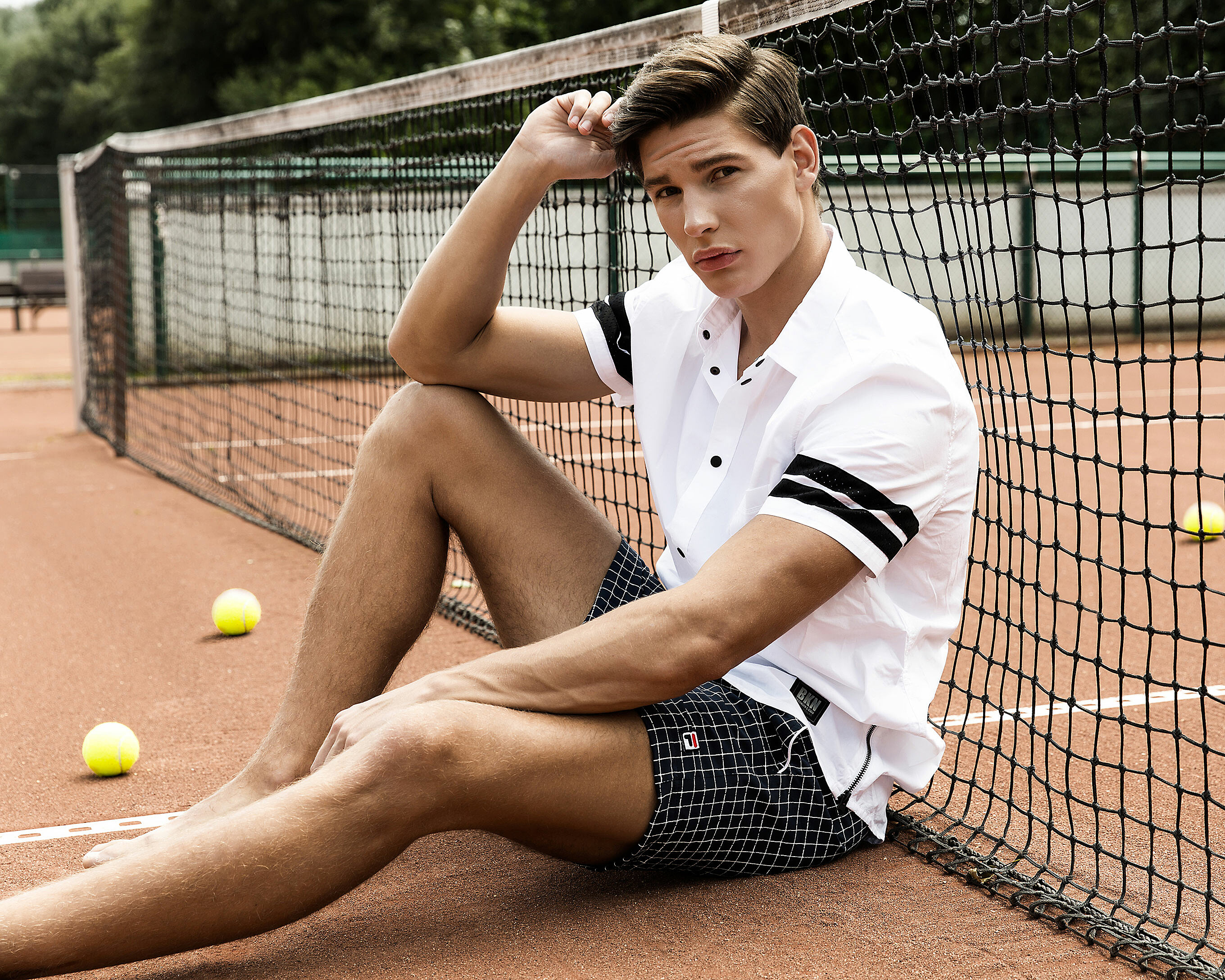 A male model who sit in front of the mesh on the tennis court in a white shirt with short arms and black checked shorts
