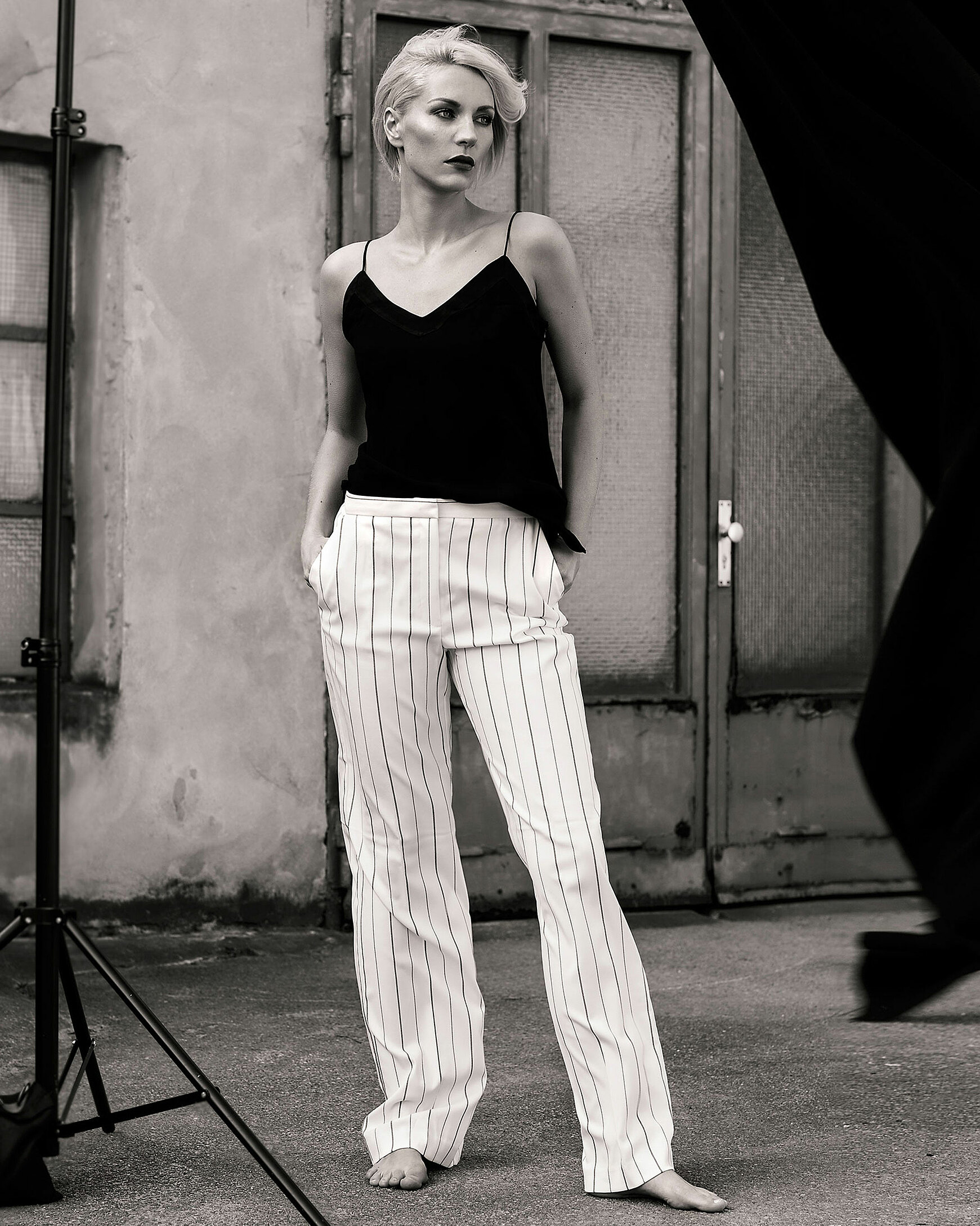 A black and white photo of a blonde woman in white long trousers with stripes and a black triangle top in front of a door in a backyard