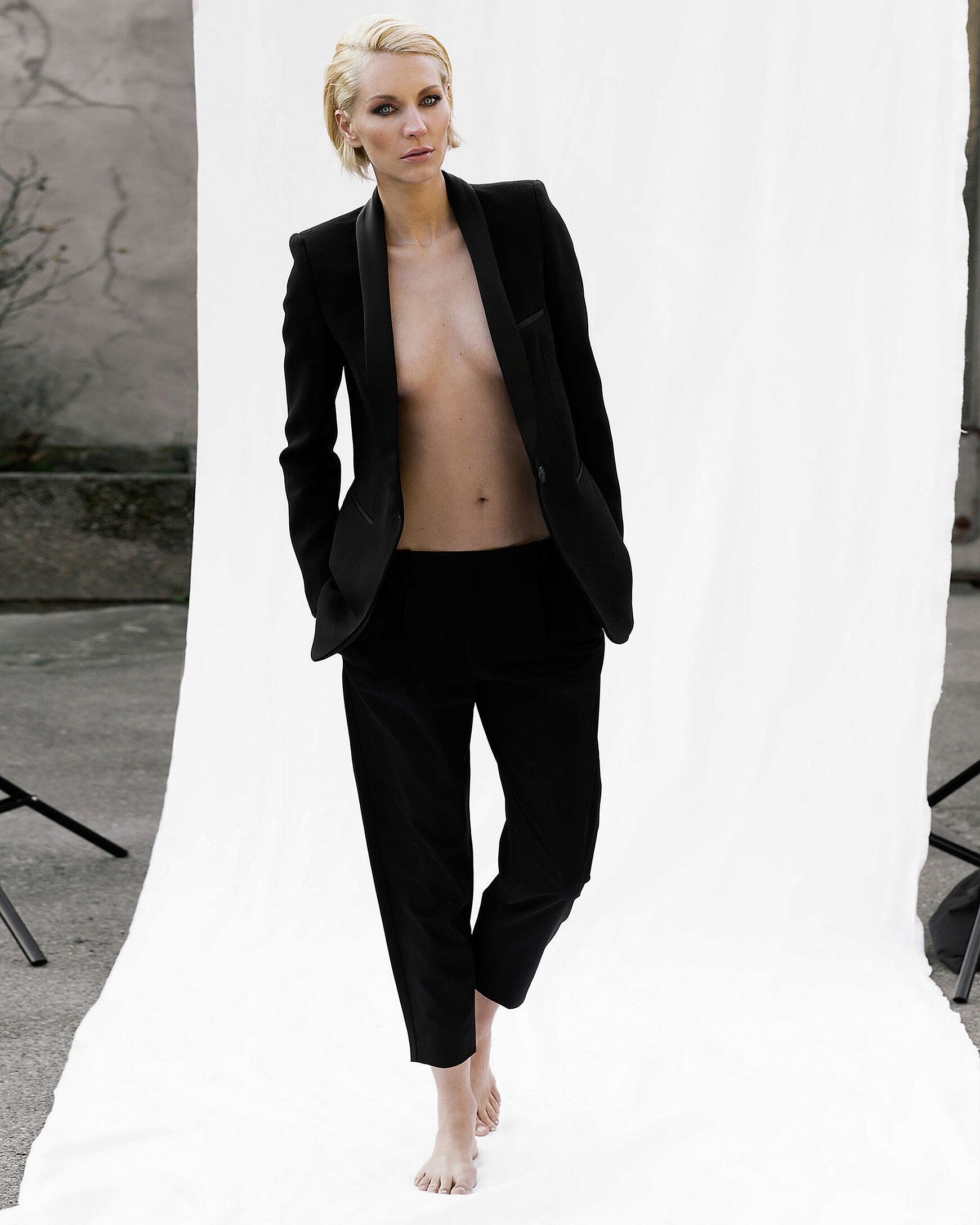 A blonde woman in a black suit with nothing else in front of a white background