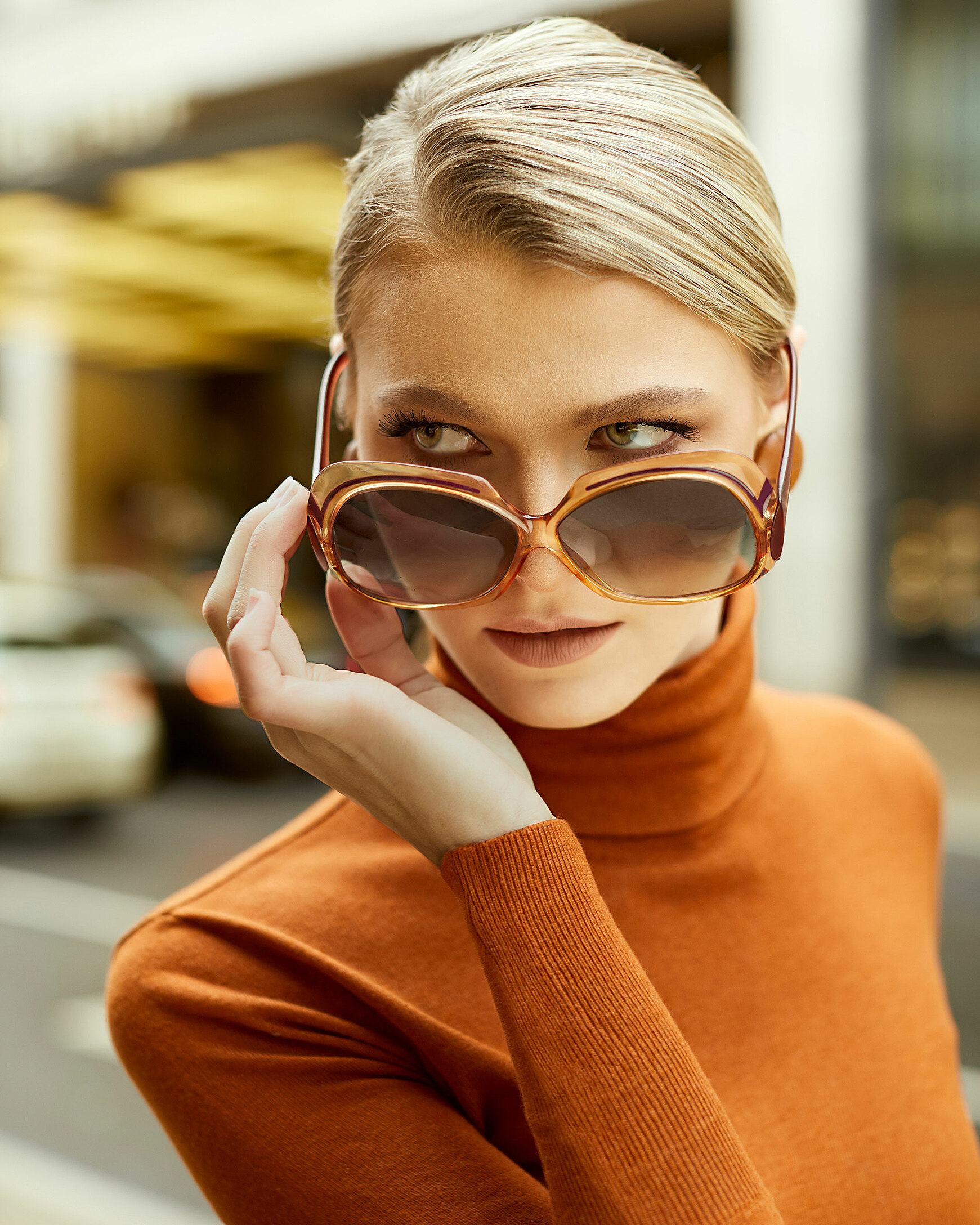 A portrait of a blond hair model with orange big sunglasses and an orange pullover with a turtleneck in an outdoor location in front of a hotel with yellow lights