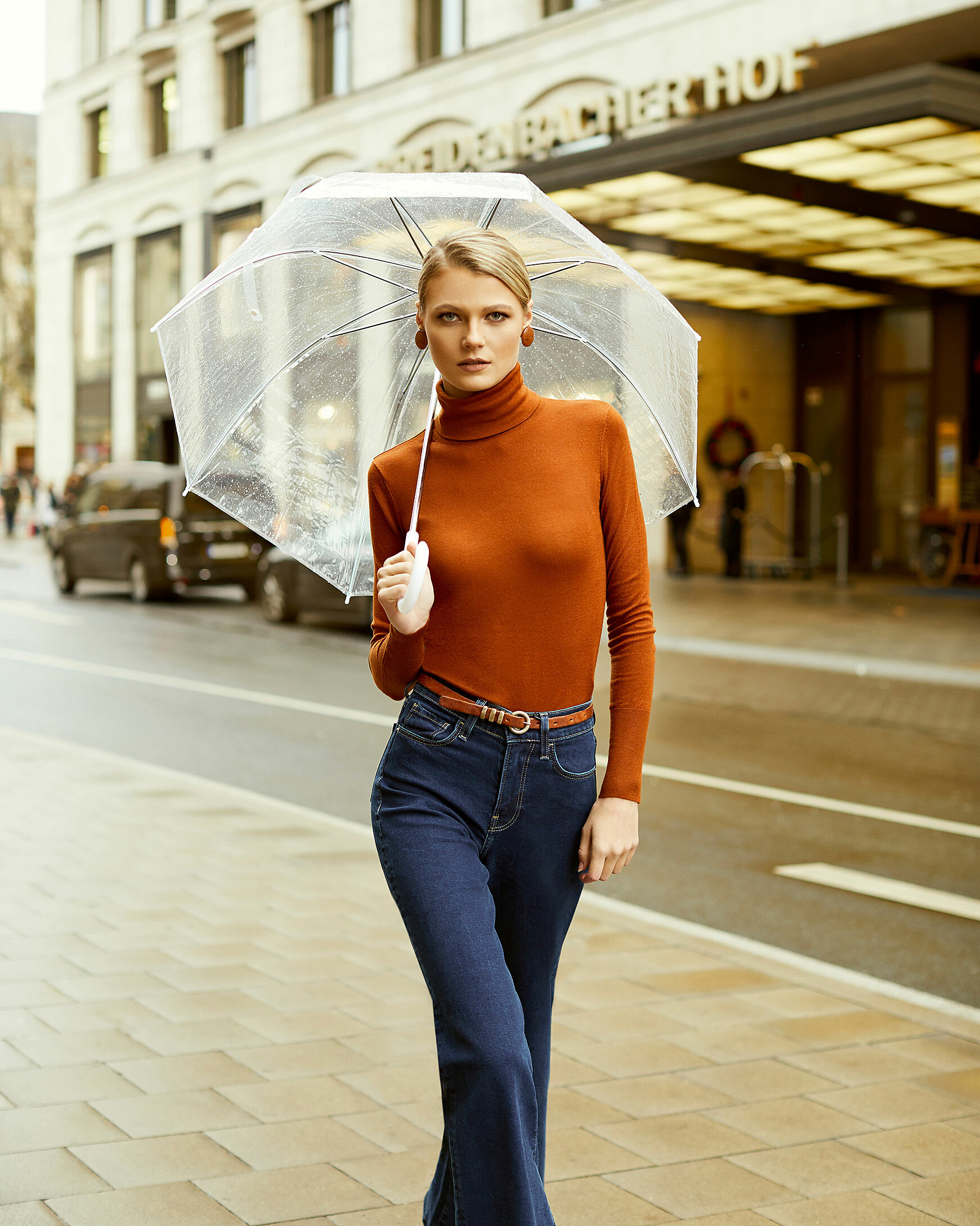 A blond hair model with a transparent umbrella and an orange pullover with a turtleneck with blue trousers in an outdoor location in front of a hotel with yellow lights