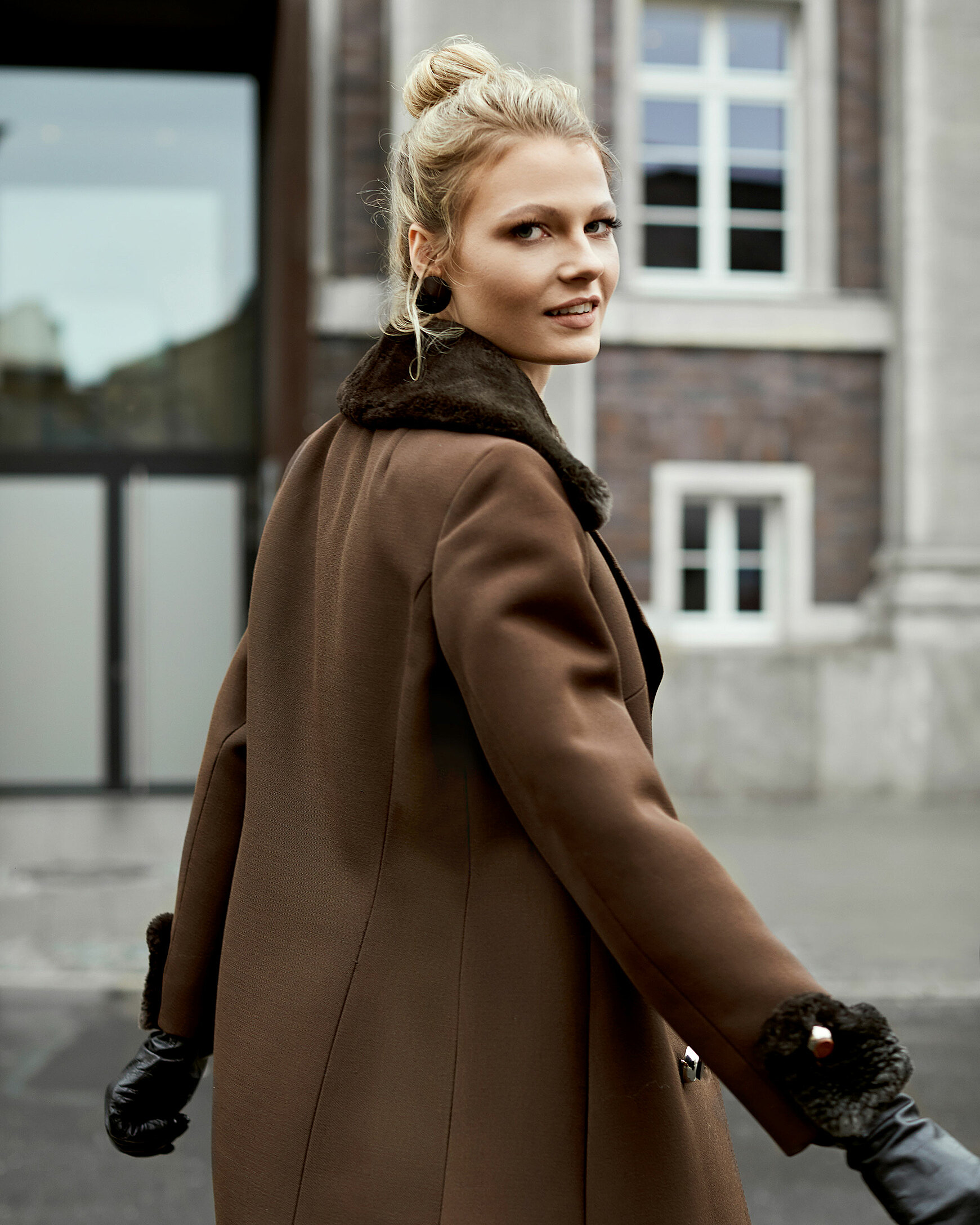 A blonde model in a brown winter coat with fake fur applications and a pair of leather gloves in front of a building