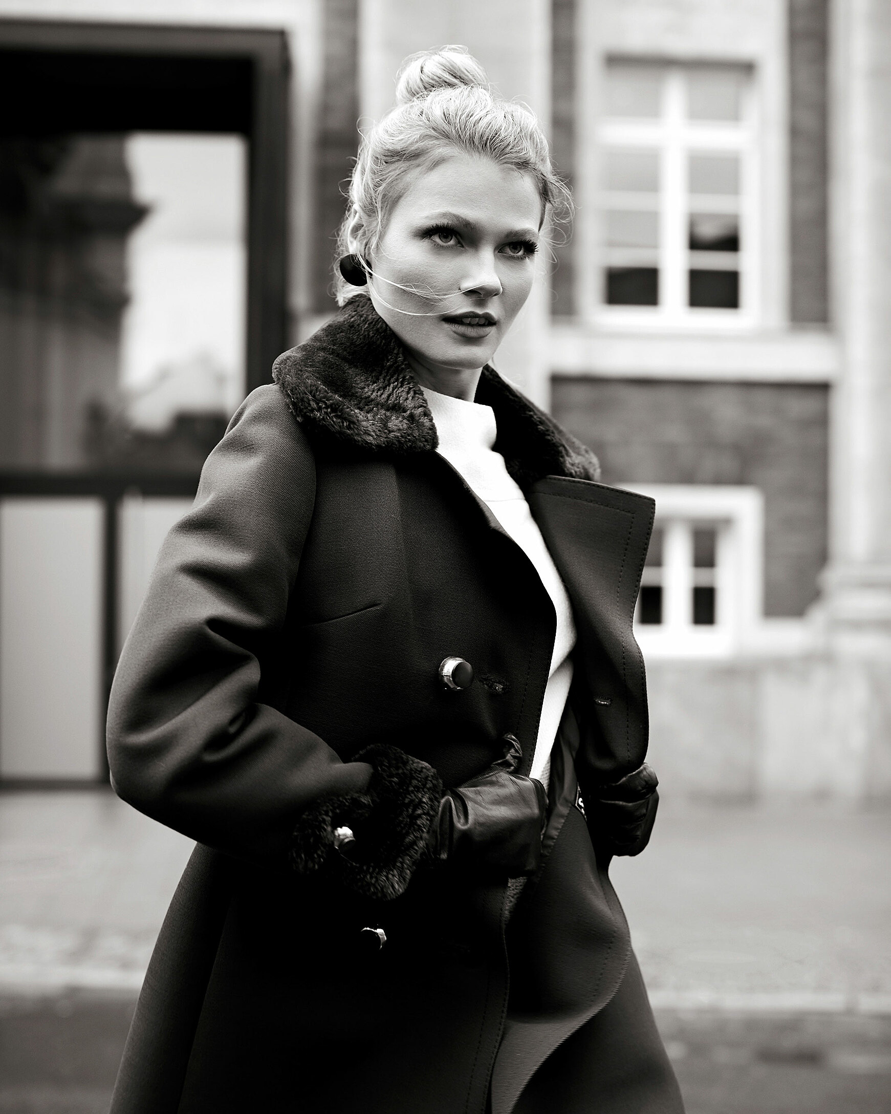 A black and white photo of a blonde model in a winter coat with fake fur applications and a pair of leather gloves in front of a building. She jumps next to the camera