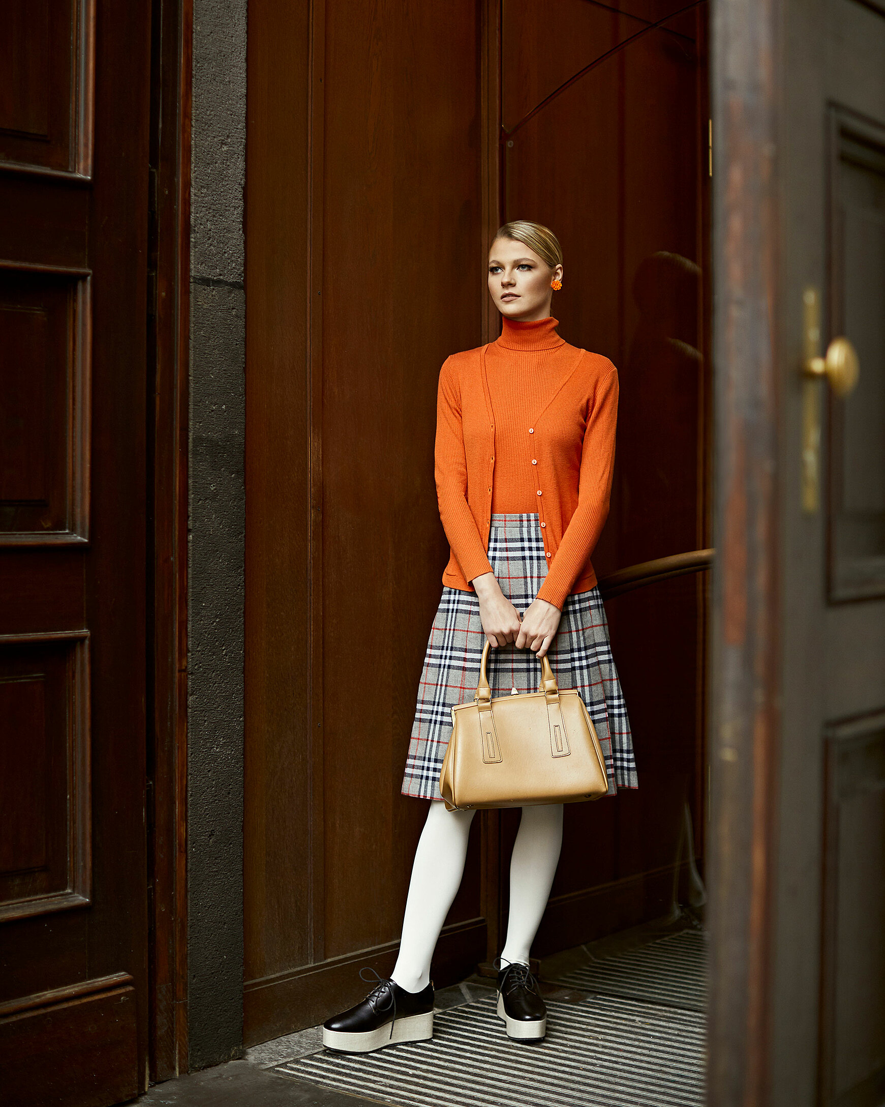 A blonde model in the entry of a church with brown doors. The model wears an orange pullover and a similar colored cardigan. Big orange ear clips and a nude colored handbag. She wears it like a quite shy person in a long skirt and white tights in black plateau shoes