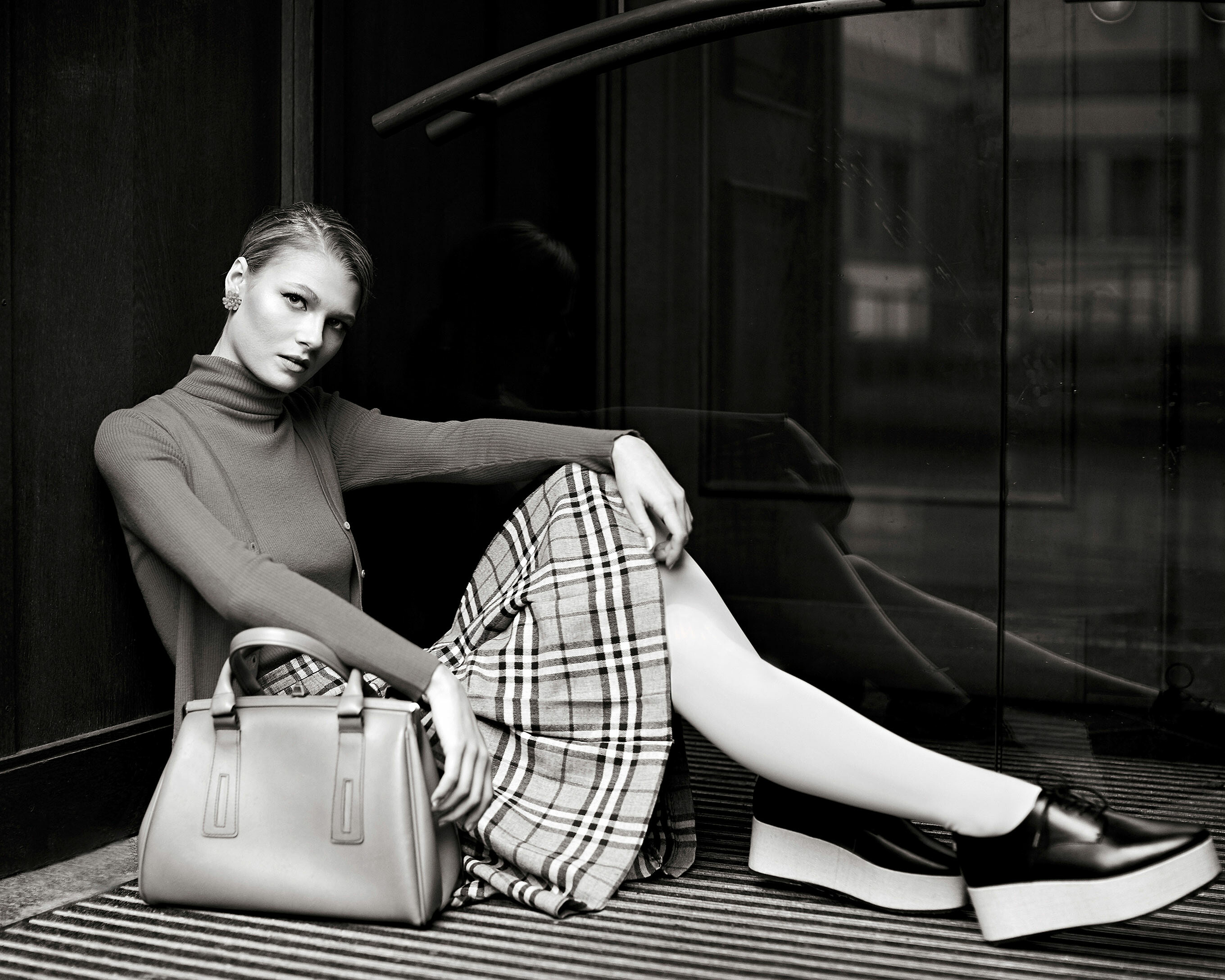 A blonde model sit in the entry of a church. The model wears a pullover and a cardigan combine with a checked skirt, white tights and dark shoes. Hey handbag stand in front of her hips
