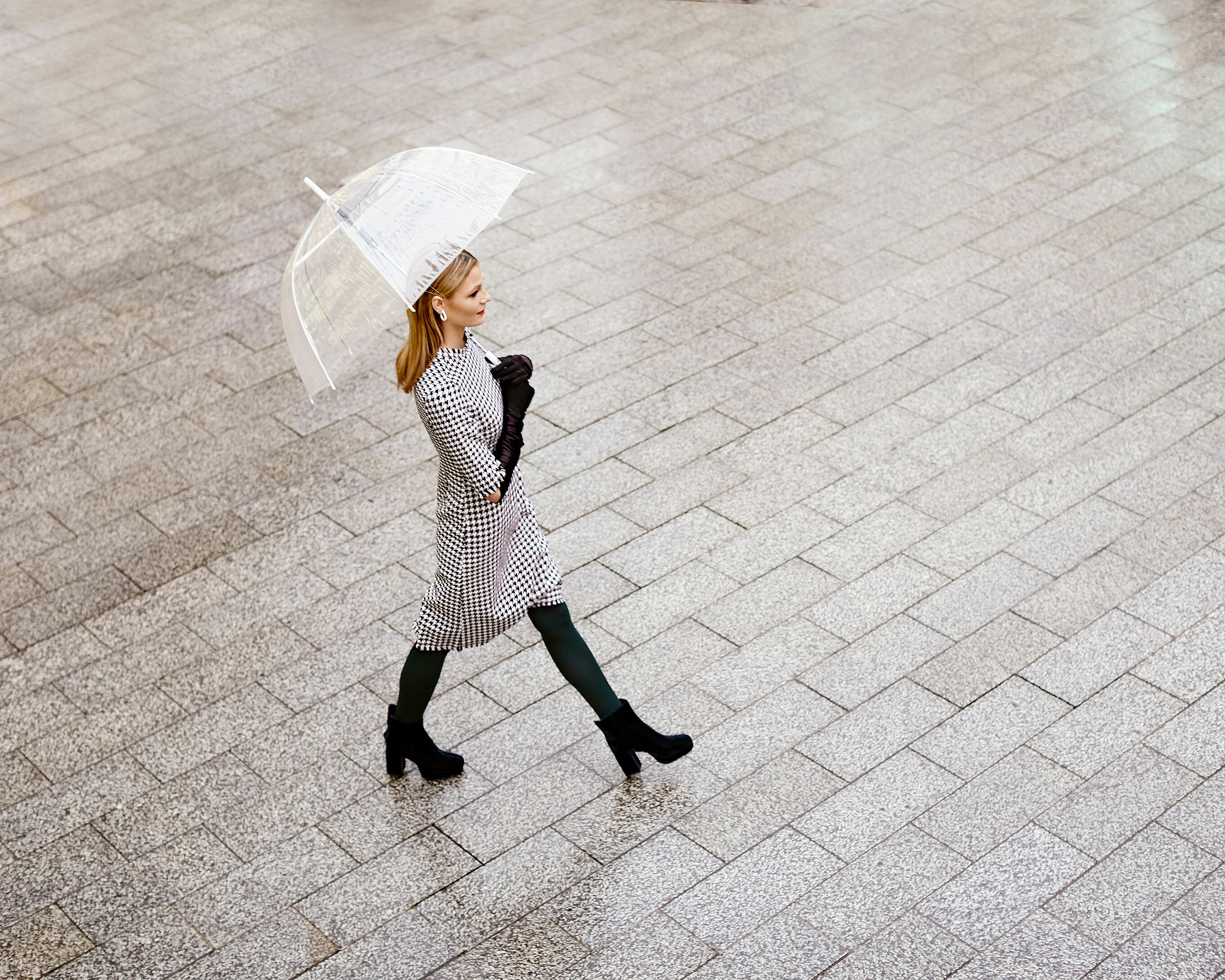 A blonde model walks in a grey long dress with black tights, black gloves and black boots with a transparent umbrella