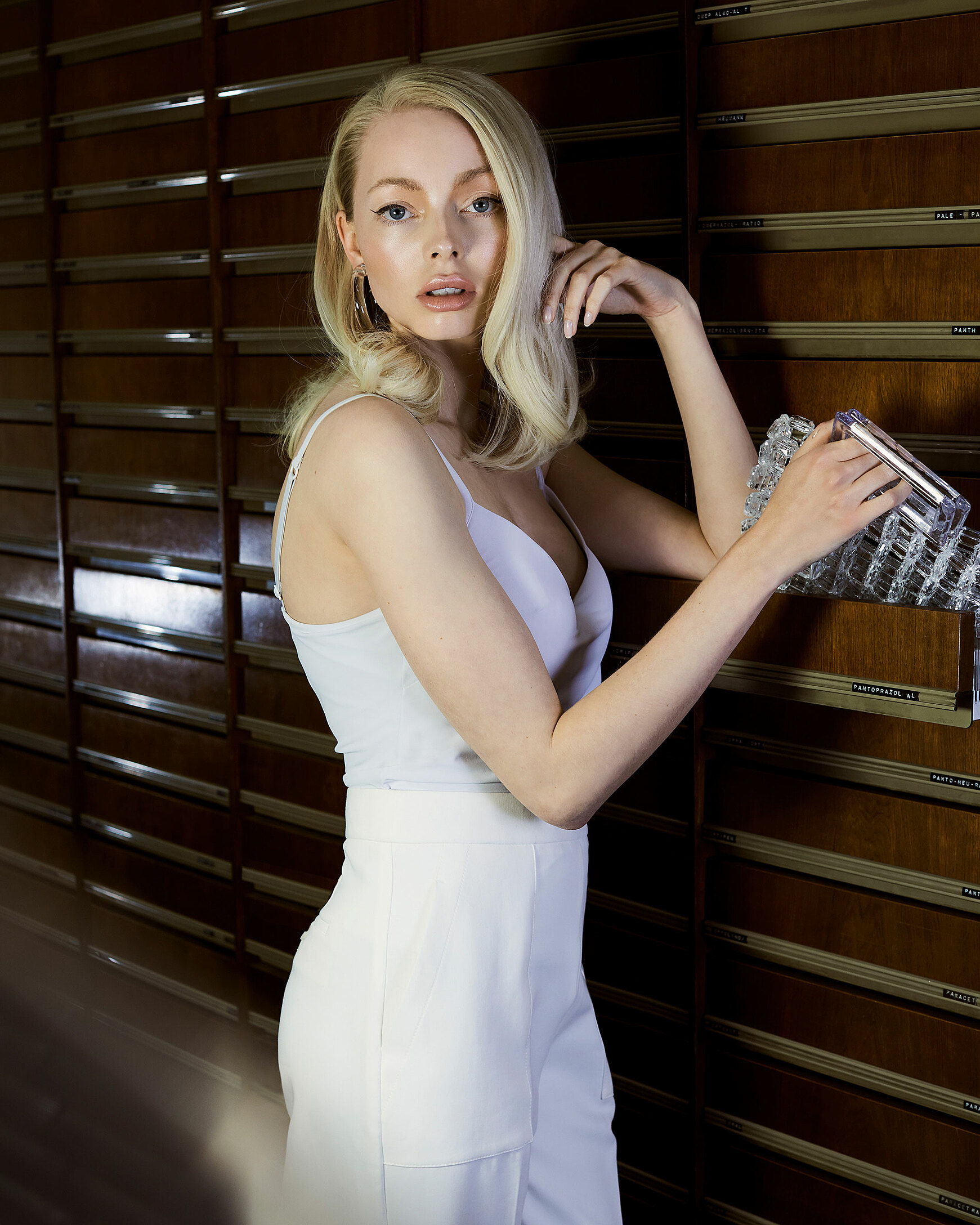 A blonde model in white trousers and tight top by triumph. She hold her transparency bag in her right hand