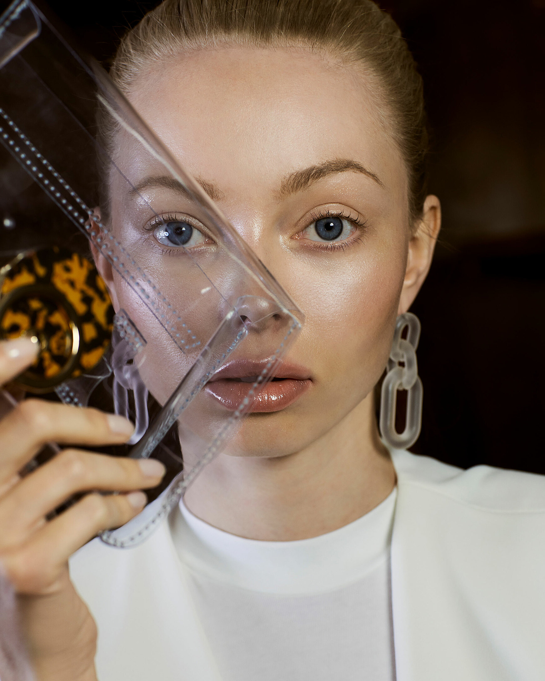 A close up of a blonde model who wears transparency earrings and hold a transparency clutch in her right hand in front of her face