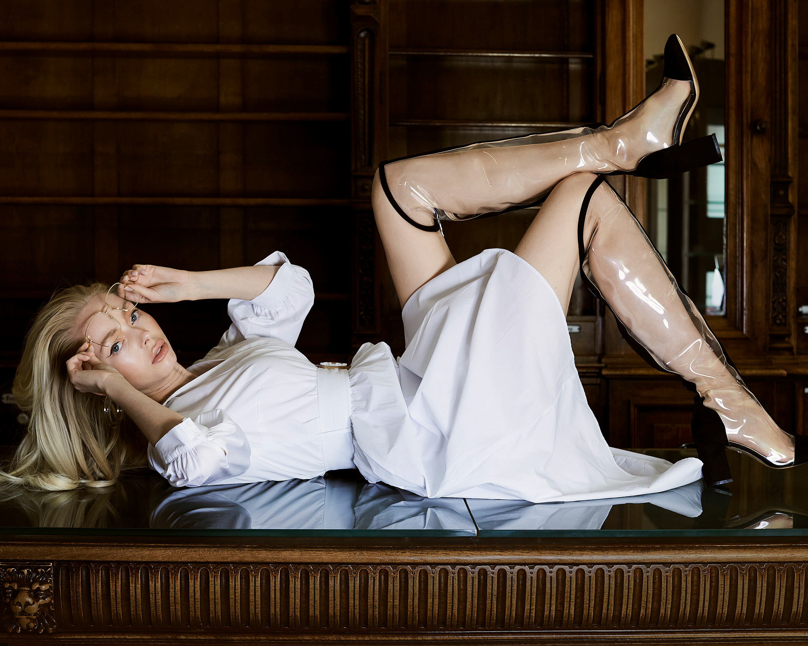 A blonde model lies on a brown table with a white dress. She wears glasses and transparency boots with black applications