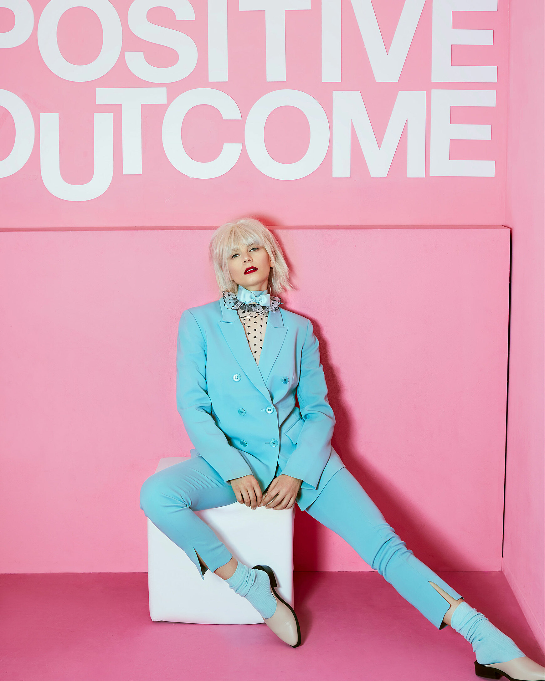"A female model with a blonde wig sits on a cube in a complete baby blue suit in a pink room. The sentence ""positive outcome"" is written on the wall"